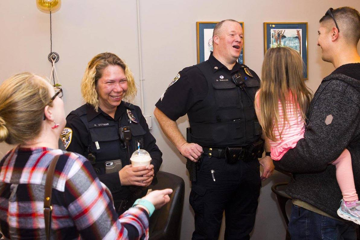 Juneau Police Department Officer Rosie Ostman and Sgt. Brian Dallas talk with Juneau residents at Sacred Grounds on Oct. 2, 2019, National Coffee with a Cop Day. The annual event promotes positive interactions with community members and law enforcement agencies. (Michael S. Lockett | Juneau Empire)