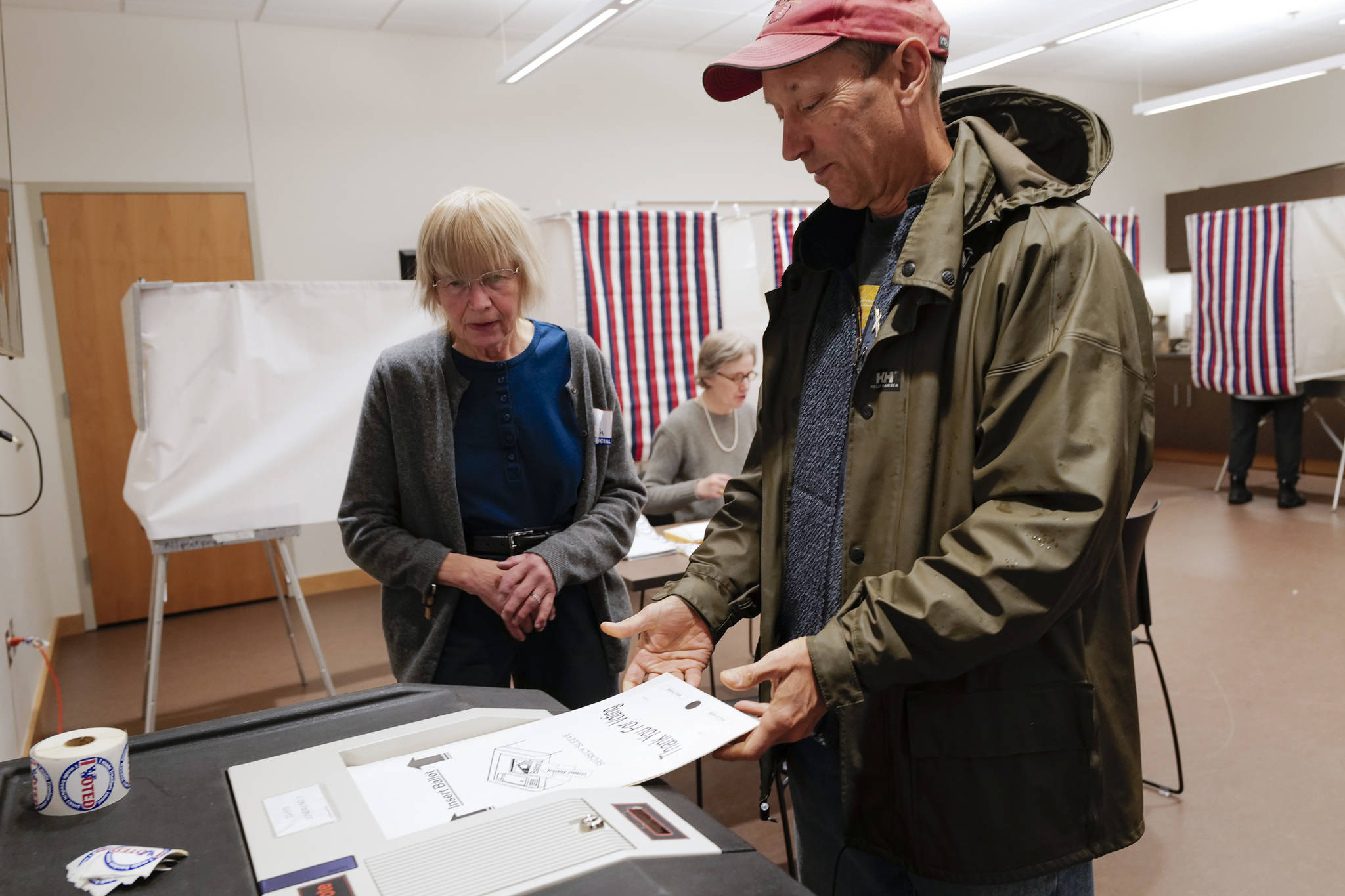 Election official Deborah Behr watches as Doug Woodby enters his ballot into a voting machine at the APK State Library, Archives and Museum Building on Tuesday, Oct. 1, 2019. (Michael Penn   Juneau Empire)