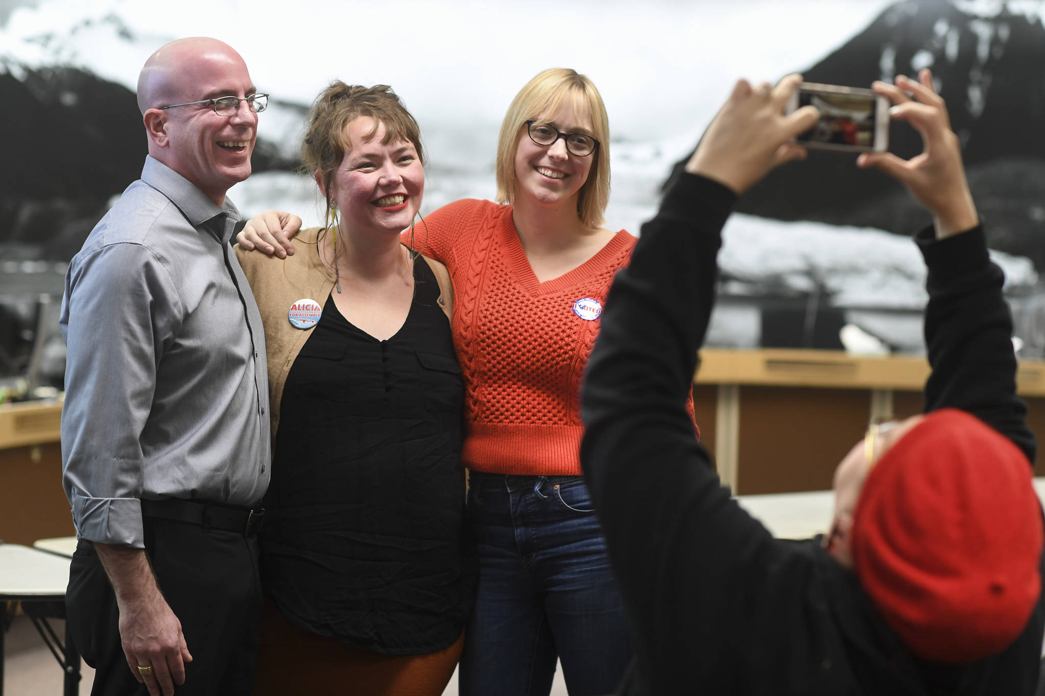 Kirsa Hughes-Skandijs takes a picture of her sister, Alicia Hughes-Skandijs, center, with Wade Bryson and Carole Triem as results come in at City Hall on Tuesday, Oct. 1, 2019. (Michael Penn | Juneau Empire)