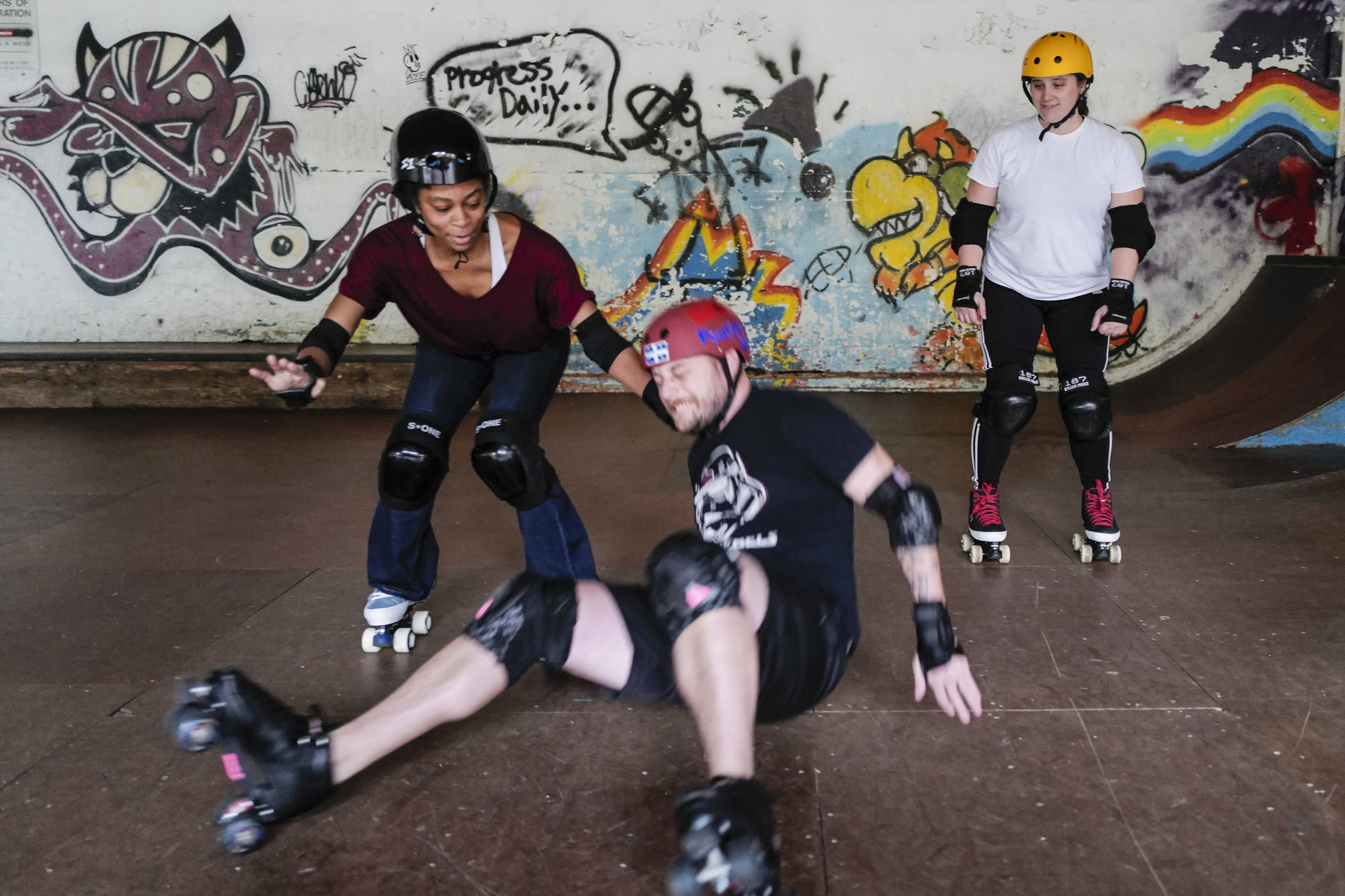 Empire reporter Michael S. Lockett takes a fall while being taught to rollerskate by Jennifer Gross, left, and Shabadrang Khalsa at the Pipeline Skate Park on Friday, Oct. 11, 2019. (Michael Penn | Juneau Empire)