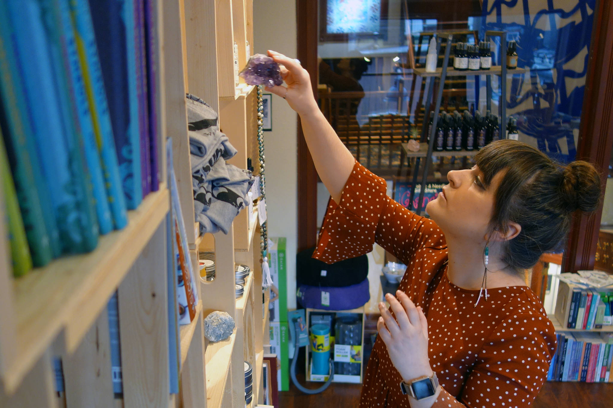 Brianna Ackley, owner of Wolfsong Wellness Boutique puts a crystal away on Thursday, Oct. 17, 2019. (Ben Hohenstatt | Juneau Empire)(Ben Hohenstatt | Juneau Empire)