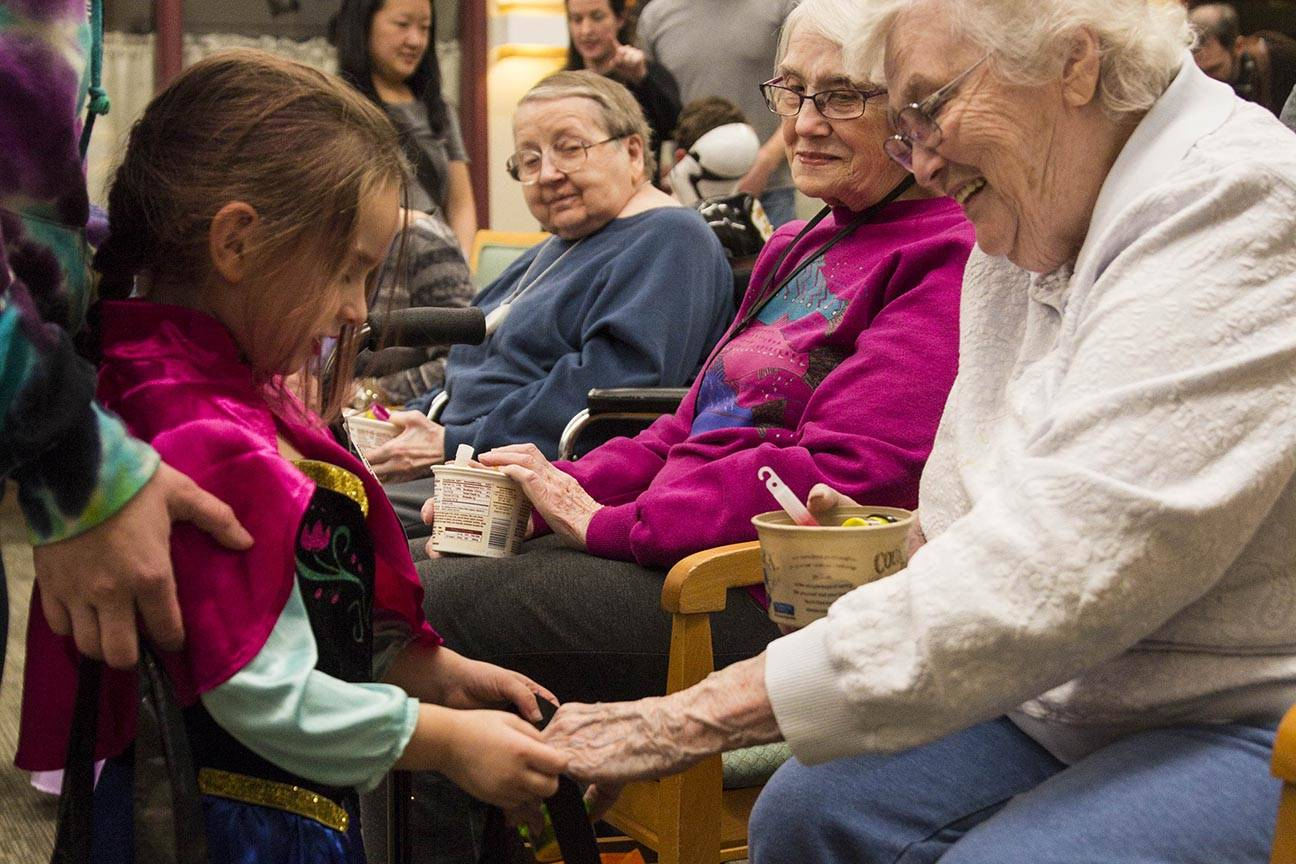 Lilly, 3, receives some candy from Betty Hunt as members of the Parents as Teachers program and a number of children visited the Juneau Pioneer Home to have an early Halloween with the residents on Tuesday, Oct. 22, 2019. (Michael S. Lockett | Juneau Empire)