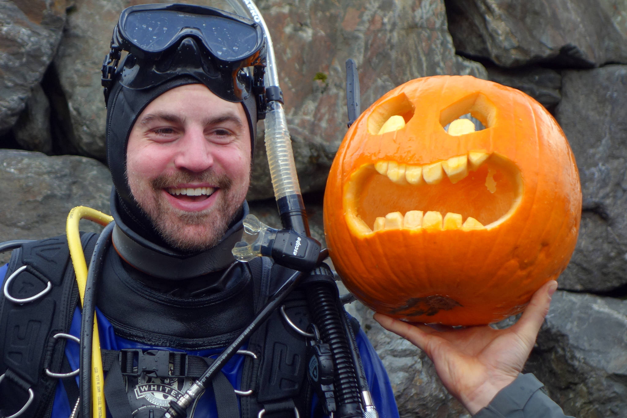 Darren Jaeckel smiles near a jack-o'-lantern he carved underwater at the Sixth Annual Spooktacular Dive and Underwater Pumpkin Carving event Saturday, Oct. 26, 2019. (Ben Hohenstatt | Juneau Empire)