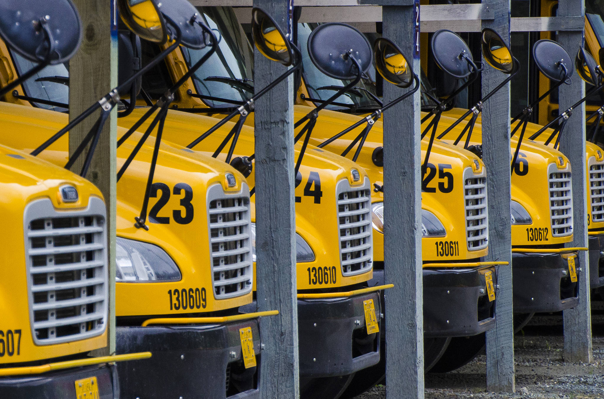School buses sit idle at the First Student lot on Mendenhall Loop Road in this May 2014 photo. (Michael Penn \ Juneau Empire File)