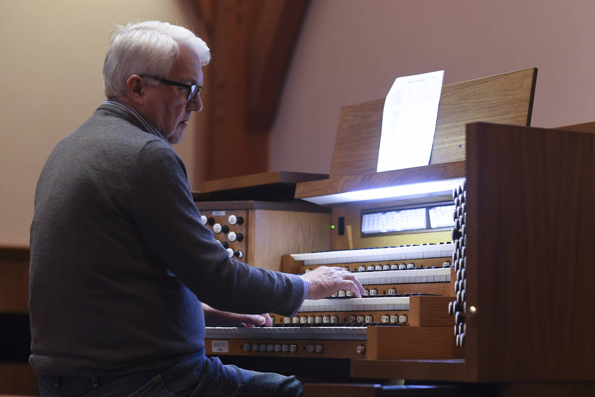 Jonas Nordwall, organist and artistic director of music for the First United Methodist Church in Portland, Oregon, works on Thursday at preparing a 2013 Allen Bravura Organ for its first public concert at Holy Trinity Episcopal Church. Learn more by watching the video below. (Michael Penn | Juneau Empire)