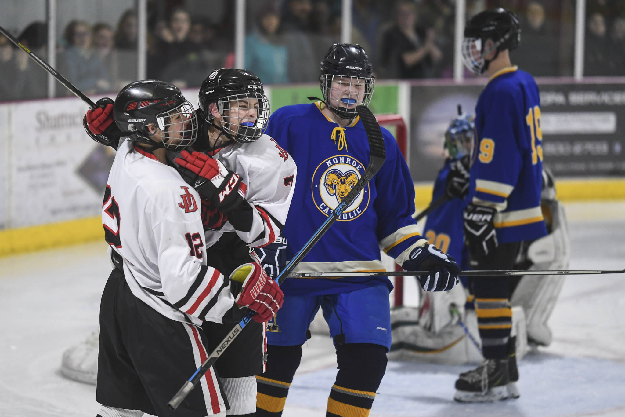 Juneau-Douglas' Fin Shibler, second from left, celebrates his third period goal with teammate Joey Meier against Monroe Catholic at the Treadwell Arena on Friday, Nov. 15, 2019. JDHS won 13-0. (Michael Penn | Juneau Empire)