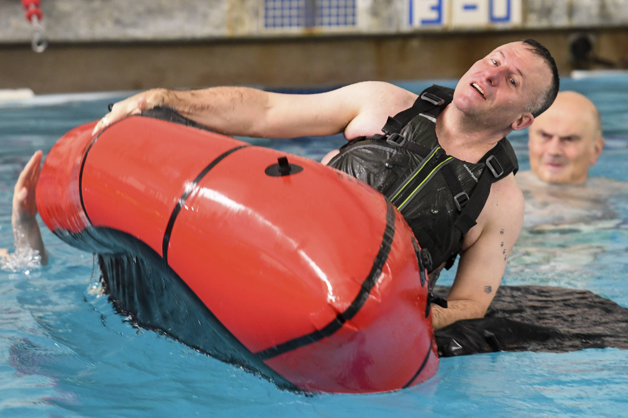 Lt. Cmdr. Scott Shields, a Coast Guard officer stationed in Juneau, flips a small boat during a boating safety training class at the Augustus Brown Swimming Pool on Tuesday, Nov. 19, 2019. The class will qualify the members to teach students around the state about the use and importance of life vests. (Michael Penn | Juneau Empire)