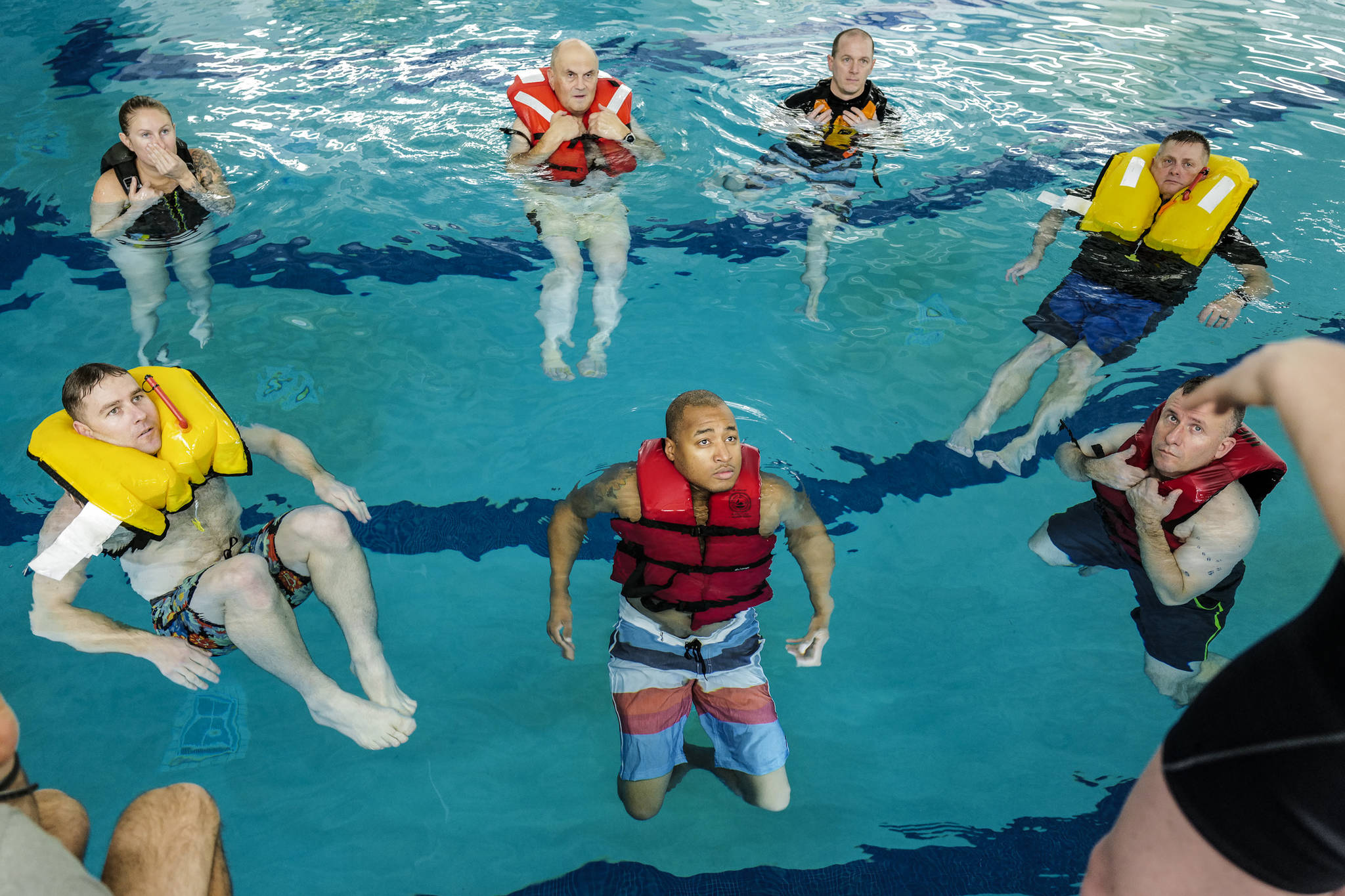 Members of the U.S. Coast Guard stationed in Juneau take a boating safety training class at the Augustus Brown Swimming Pool on Tuesday, Nov. 19, 2019. The class will qualify the members to teach students around the state about the use and importance of life vests. (Michael Penn | Juneau Empire)