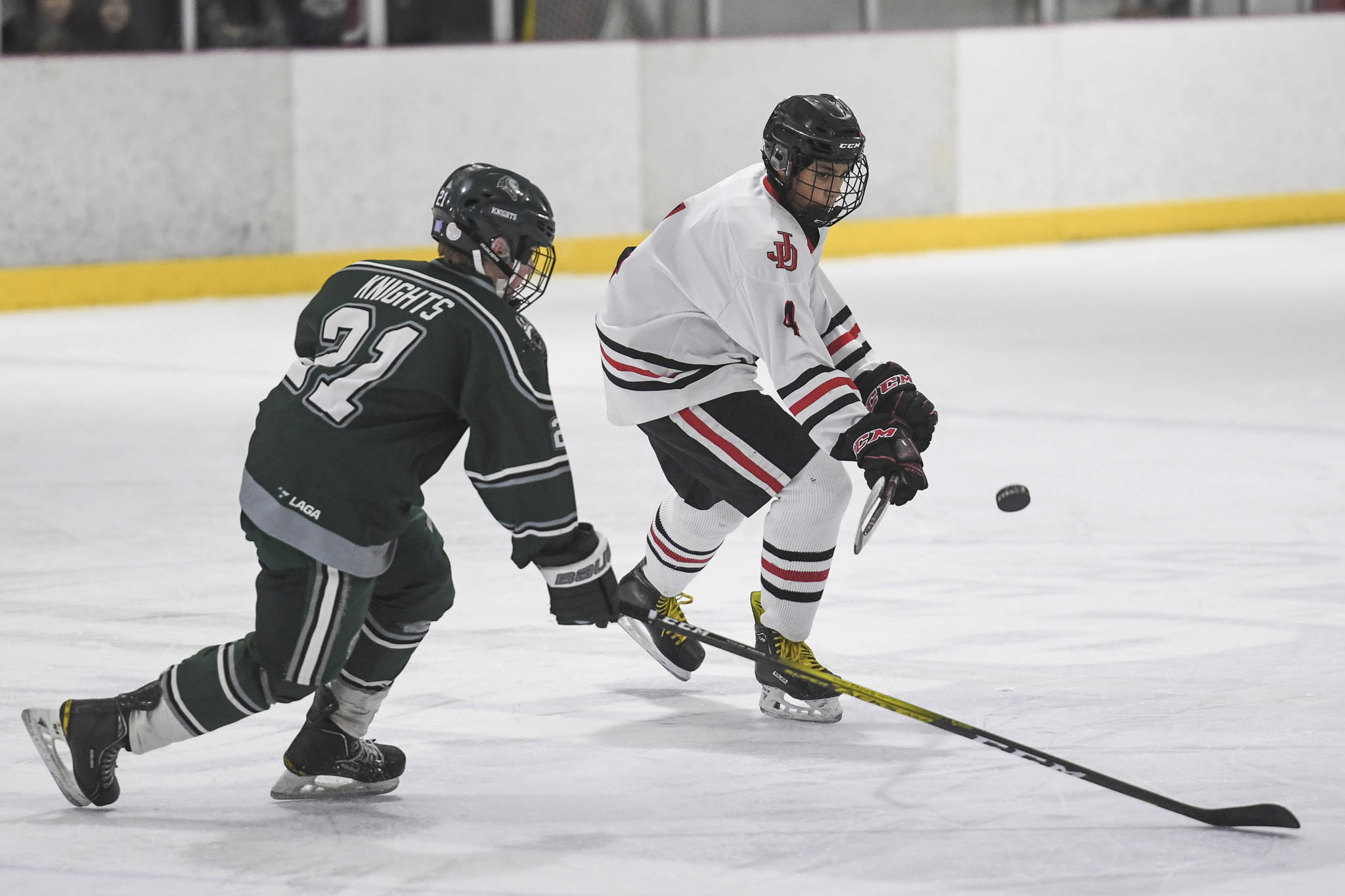 Juneau-Douglas' Andre Peirovi, right, flicks the puck away from Colony's Jacob Ross at Treadwell Arena on Friday, Nov. 22, 2019. (Michael Penn | Juneau Empire)
