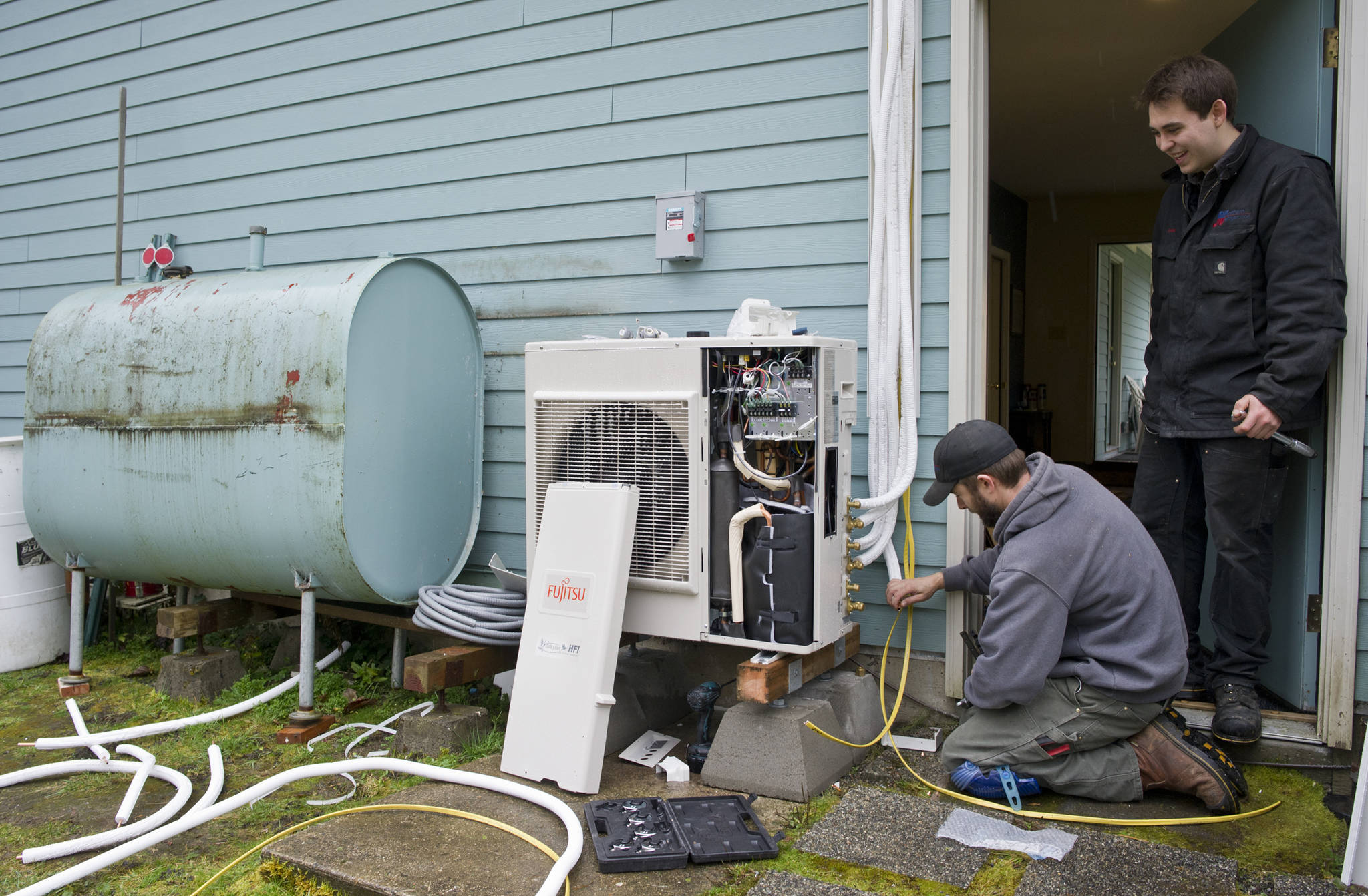 Jake Eames, right, and David Nash install an air-to-air heat pump system to a Mendenhall Valley home Thursday that formerly was using oil for heating in 2015. (Michael Penn | Juneau Empire)