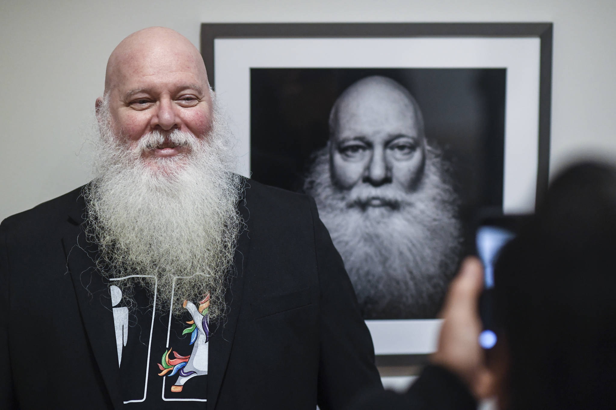 Mike Gates of Ketchikan has his picture taken by friend Dan Dawson in front of his self portrait at the Alaska Positive juried photography exhibit at the Alaska State Museum during Gallery Walk on Friday, Dec. 6, 2019. Gates received an Award of Recognition for his self portrait. (Michael Penn | Juneau Empire)