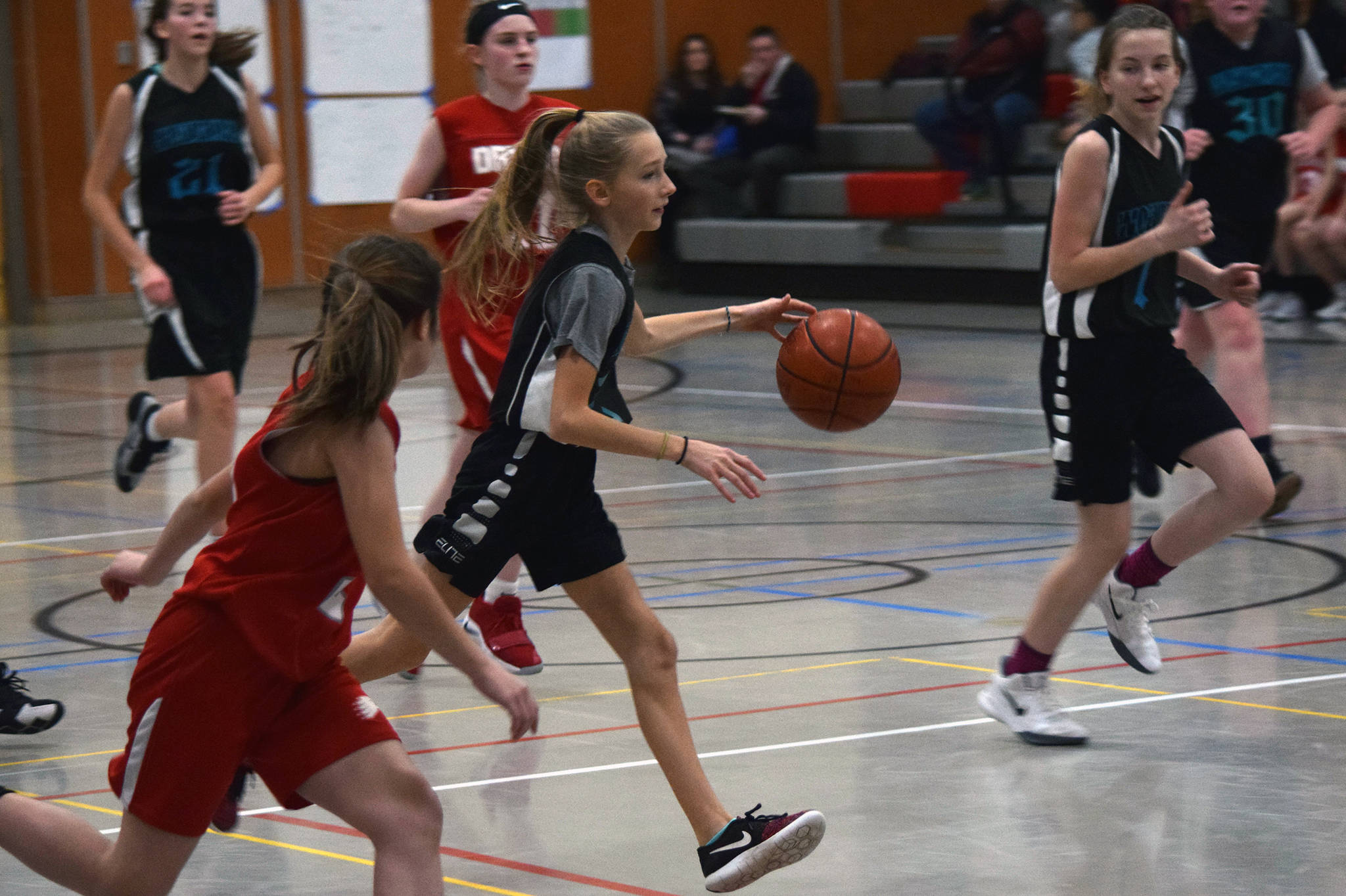 Dzantik'i Heeni's Rayna Tuckwood pushes the ball as teammate Jenna Dobson, far right, keeps pace during a round-robin game at the Icebreaker Tournament at FDMS on Friday, Dec. 6, 2019. (Nolin Ainsworth | Juneau Empire)