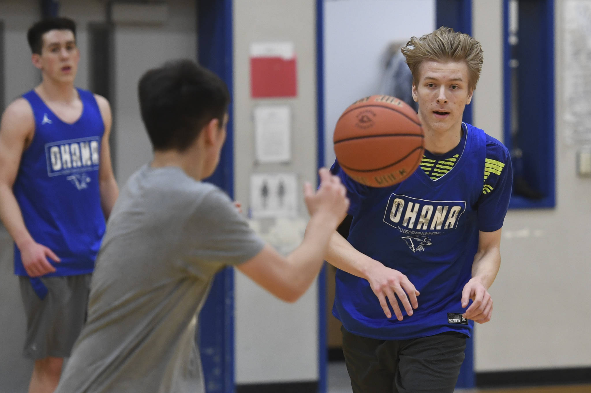 Stone Morgan, right, makes a pass during boys varsity basketball practice at Thunder Mountain High School on Tuesday, Dec. 10, 2019. (Michael Penn | Juneau Empire)