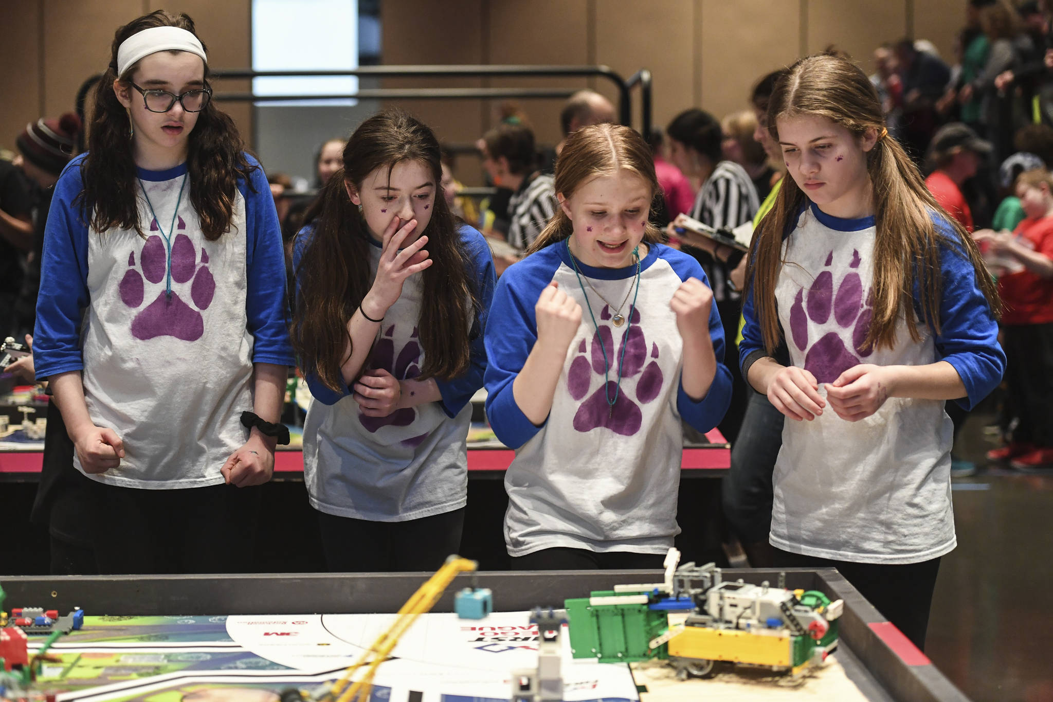 Members of the Tundra Wolves, Rosina Wolfenberger, left, Jerralyn White, Eva Miller and Kennedy White, right, cheer on their robot as they complete in the First Lego League Challenge during the Juneau Robot Jamboree at Centennial Hall on Saturday, Dec. 14, 2019. Twenty teams, two remotely, competed in the First Lego League and four more in the Junior League. the robot performance is one of four parts to the contest. The students are also graded on teamwork, a research project and robot design. Top teams will earn entry to the Alaska State Championship on Feb. 7-8, 2020, at Colony High School. (Michael Penn | Juneau Empire)