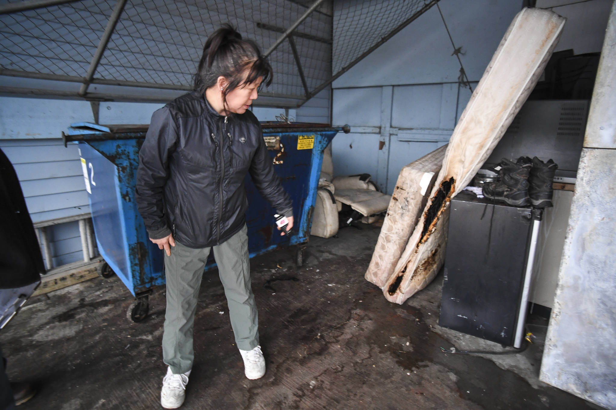Gina Chi-Mott, general manager of the Breakwater Inn, shows a burned mattress on Monday, Dec. 16, 2019, from a room fire on Sunday. (Michael Penn | Juneau Empire)