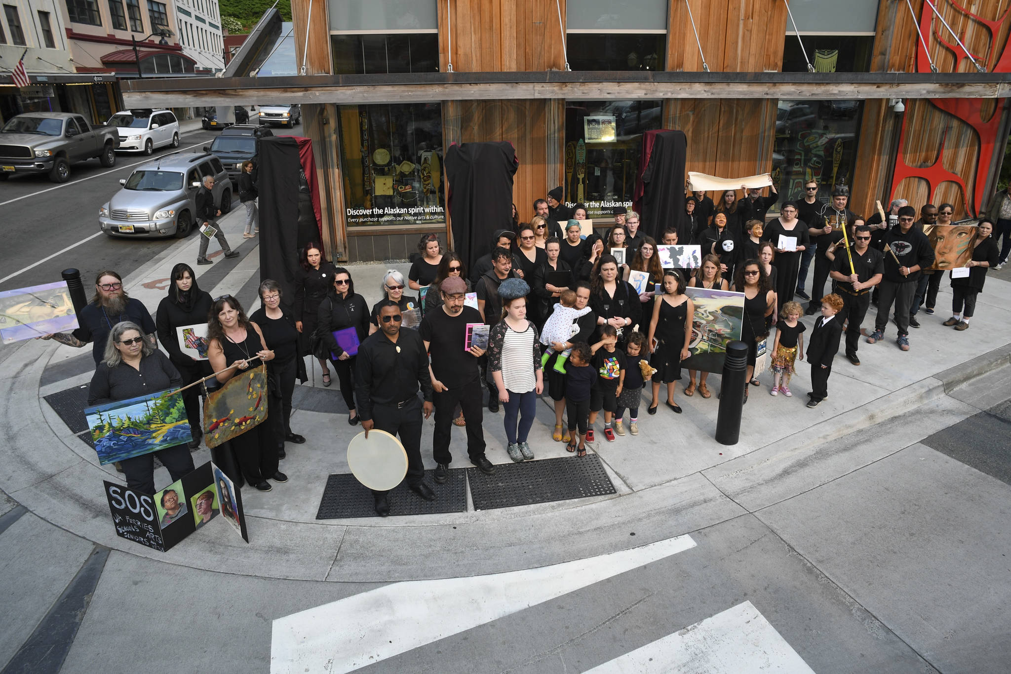About 50 artists stand with their work in front of the Sealaska Heritage Institute on Tuesday, July 9, 2019, to protest heavy cuts to state arts programs. (Michael Penn | Juneau Empire File)