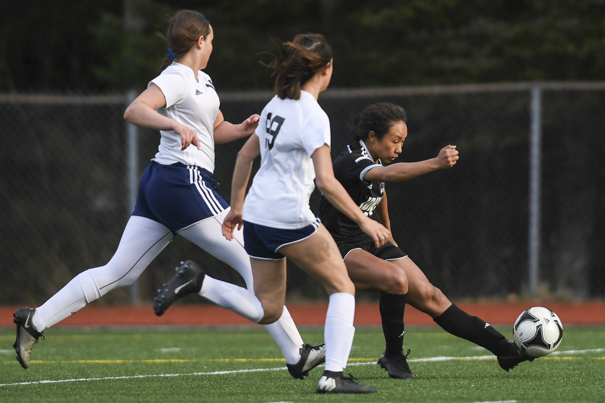 Juneau-Douglas' Malia Miller, right, shoots and scores against Soldotna's Sierra Longfellow, left, and Caleigh Glassmaker at Adair-Kennedy Memorial Field on Friday, April 26, 2019. When JDHS and Soldotna rematched in the state championship match a month later, Miller scored two more goals to finish with 105 in her career, the most in Alaska girls soccer. (Michael Penn | Juneau Empire File)
