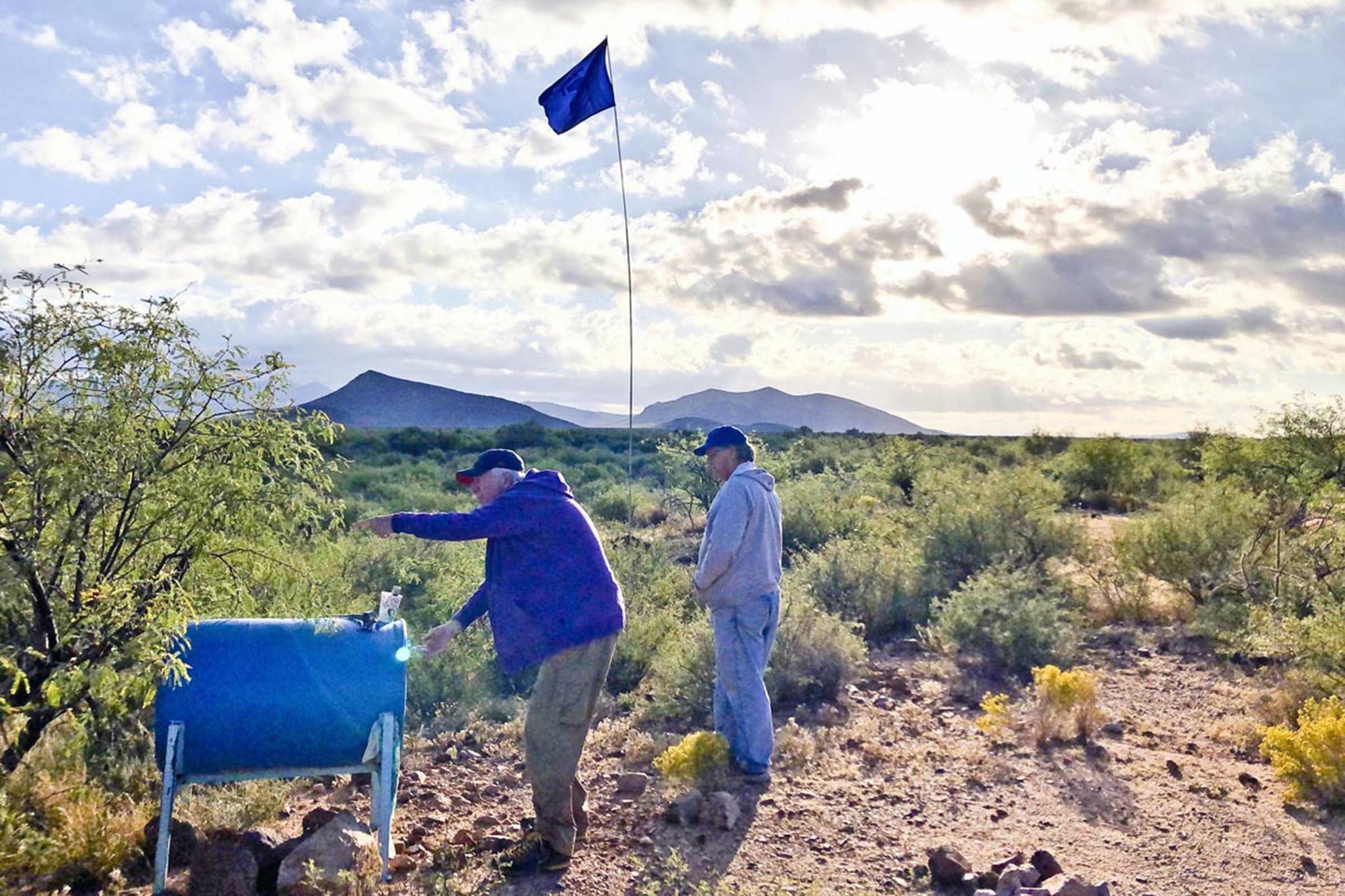 Ken Huse | Courtesy Photo                                 Volunteers from Humane Borders, a charitable organization, fill a water drum in the Arizona desert for immigrants traveling the waste.