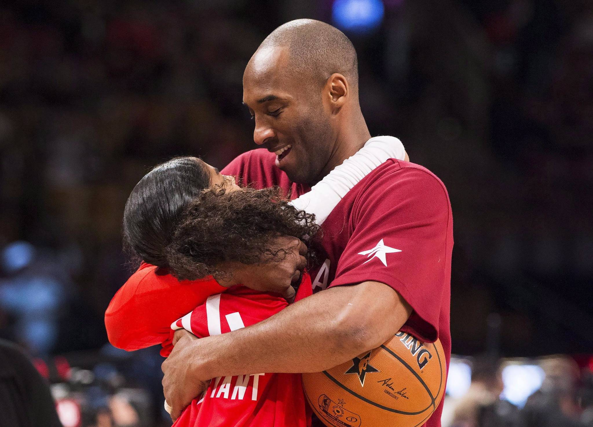 In this Feb. 14, 2016, file photo, Los Angeles Lakers Kobe Bryant (24) hugs his daughter Gianna on the court in warm-ups before first half NBA All-Star Game basketball action in Toronto. Bryant, his 13-year-old daughter, Gianna, and several others are dead after their helicopter went down in Southern California on Sunday, Jan. 26, 2020. (Mark Blinch | The Canadian Press via AP)