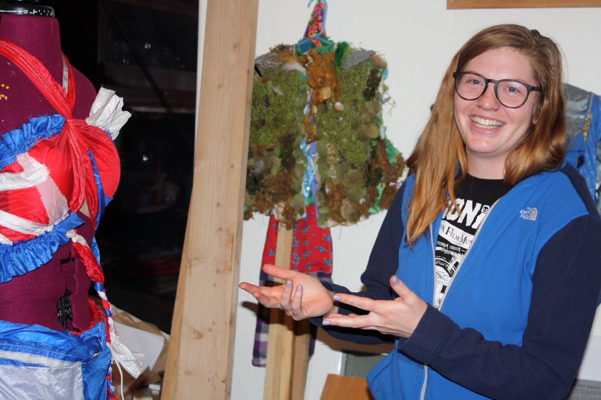 "Keren GoldbergBelle gestures at her Wearable Art 2020: Joie de Vivre piece. ""The theme is sort of Abba meets Chiquita Banana,"" GoldbergBelle said. ""That's what this is."" Past Wearable Art pieces can be seen in the background. (Ben Hohenstatt 