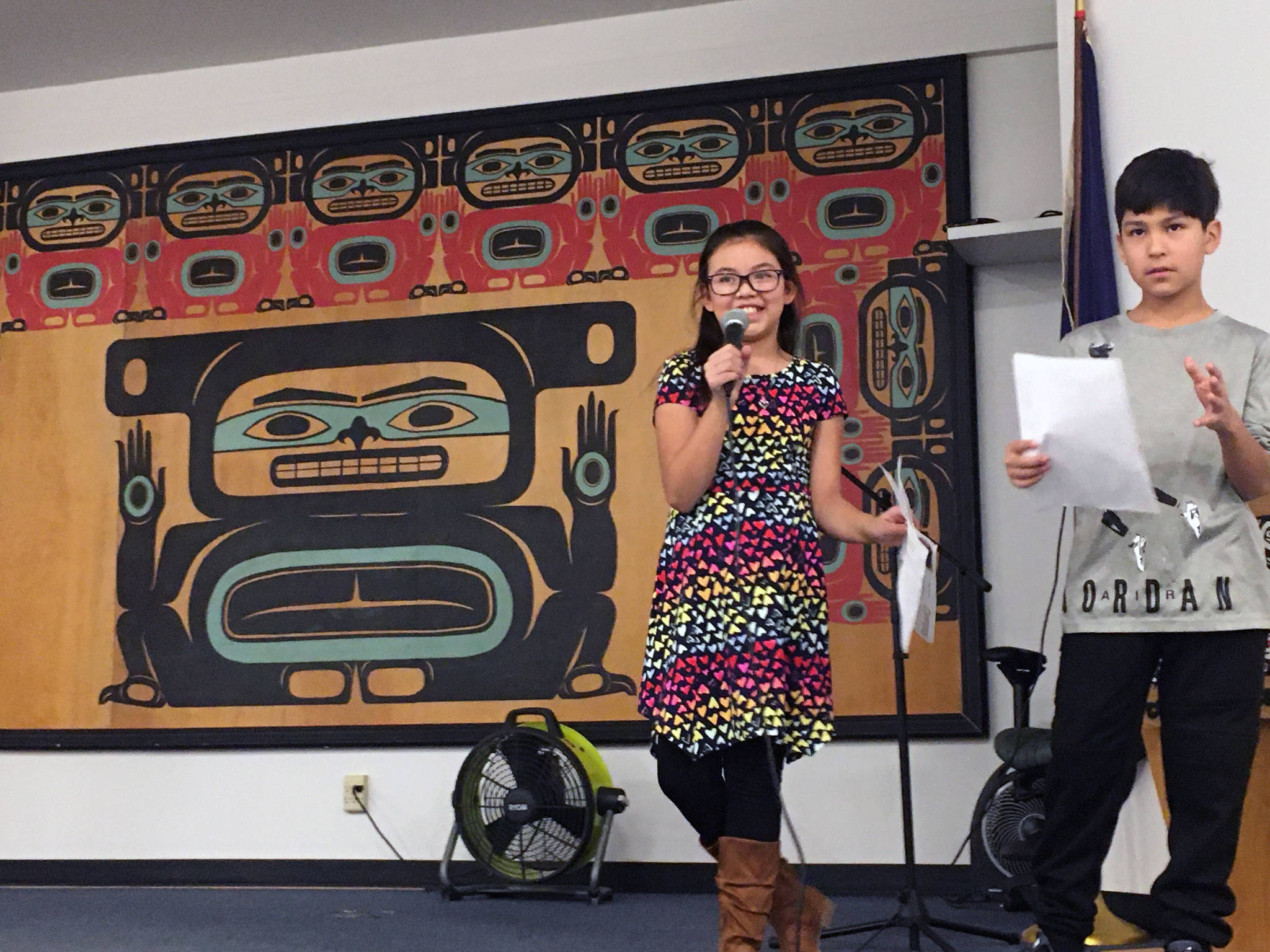 "Courtesy Photo | Lorrie Heagy                                 Glacier Valley Elementary School Sít' Eetí Shaanáx students Faith Contreras and Johnny Hunter, who are Tlingit, make a presentation at the Central Council of Tlingit and Haida Indian Tribes of Alaska elder's luncheon. They collected 64 signatures at the luncheon in support of officially adding a second verse to the state song, ""Alaska's Flag."""