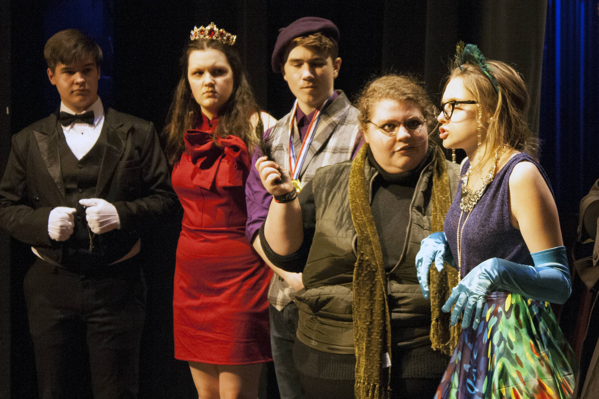 Mr. Green (Aria Moore) makes a serious accusation about Mrs. Peacock (Kayla Kohlhase) while holding a feather. A surprised Wadsworth (Toby Russell), Miss Scarlet (Amanda McDowell) and Professor Plum (Jager Hunt) look on. (Ben Hohenstatt | Juneau Empire)