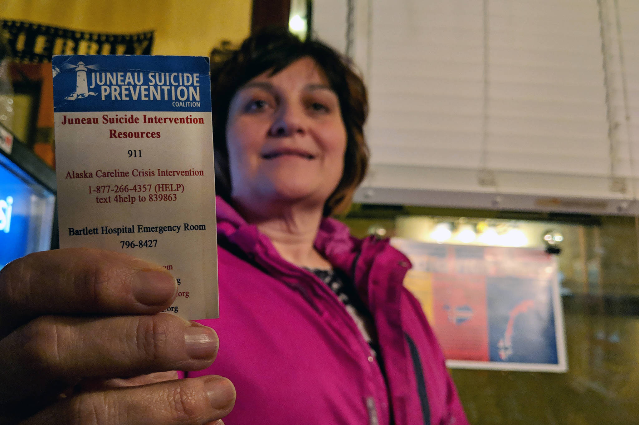 """Jan Reece, outreach/training specialist for Juneau Suicide Prevention Coalition, holds up a card with contact information for suicide prevention resources after a screening of """"The S-Word"""" at Gold Town Theater in March 2019. (Ben Hohenstatt 