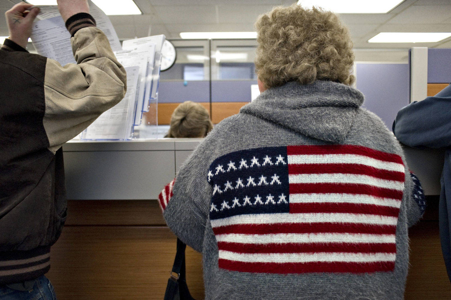 Alaskans pick up and turn in Permanent Fund Dividend applications at the Department of Revenue office in the State Office Building in March 2011. (Michael Penn | Juneau Empire File)
