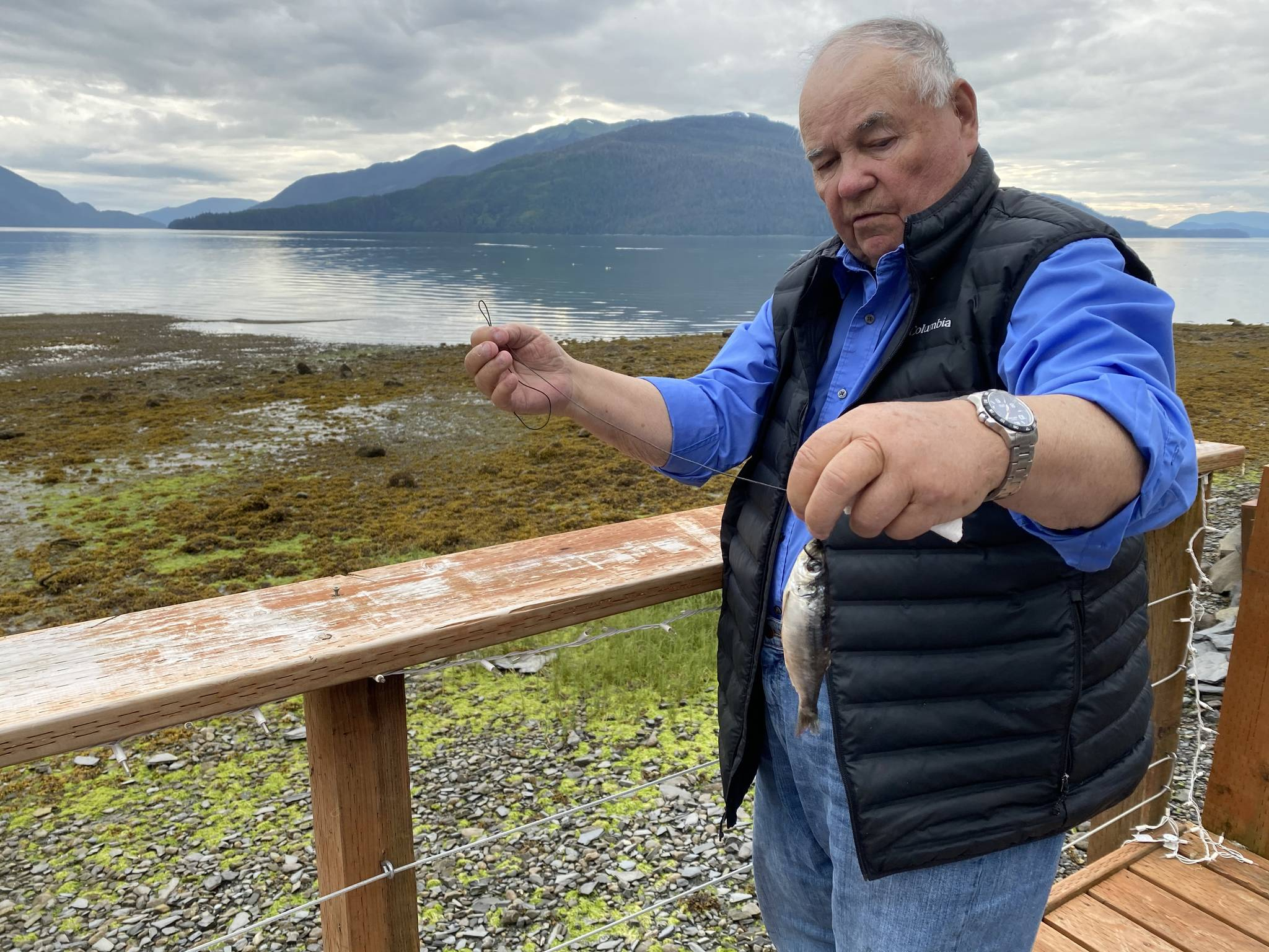 Mickey Prescott demonstrates how to choke a herring. He says choking a herring is a troller term used in the old days. He learned this technique from his dad. (Vivian Faith Prescott | For the Capital City Weekly)
