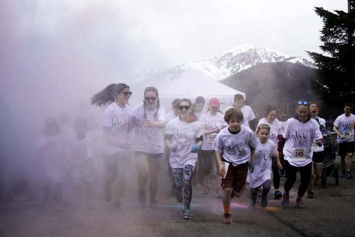 Runners jog through a haze of colored powder as they begin a 5k run through downtown Juneau on Sunday, April 29, 2018. (Richard McGrail / Juneau Empire File)