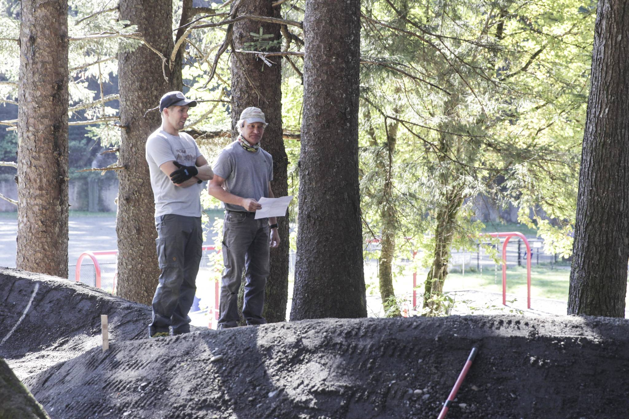 Members of the Juneau Mountain Bike Alliance check the progress of the new pump track against the plans.