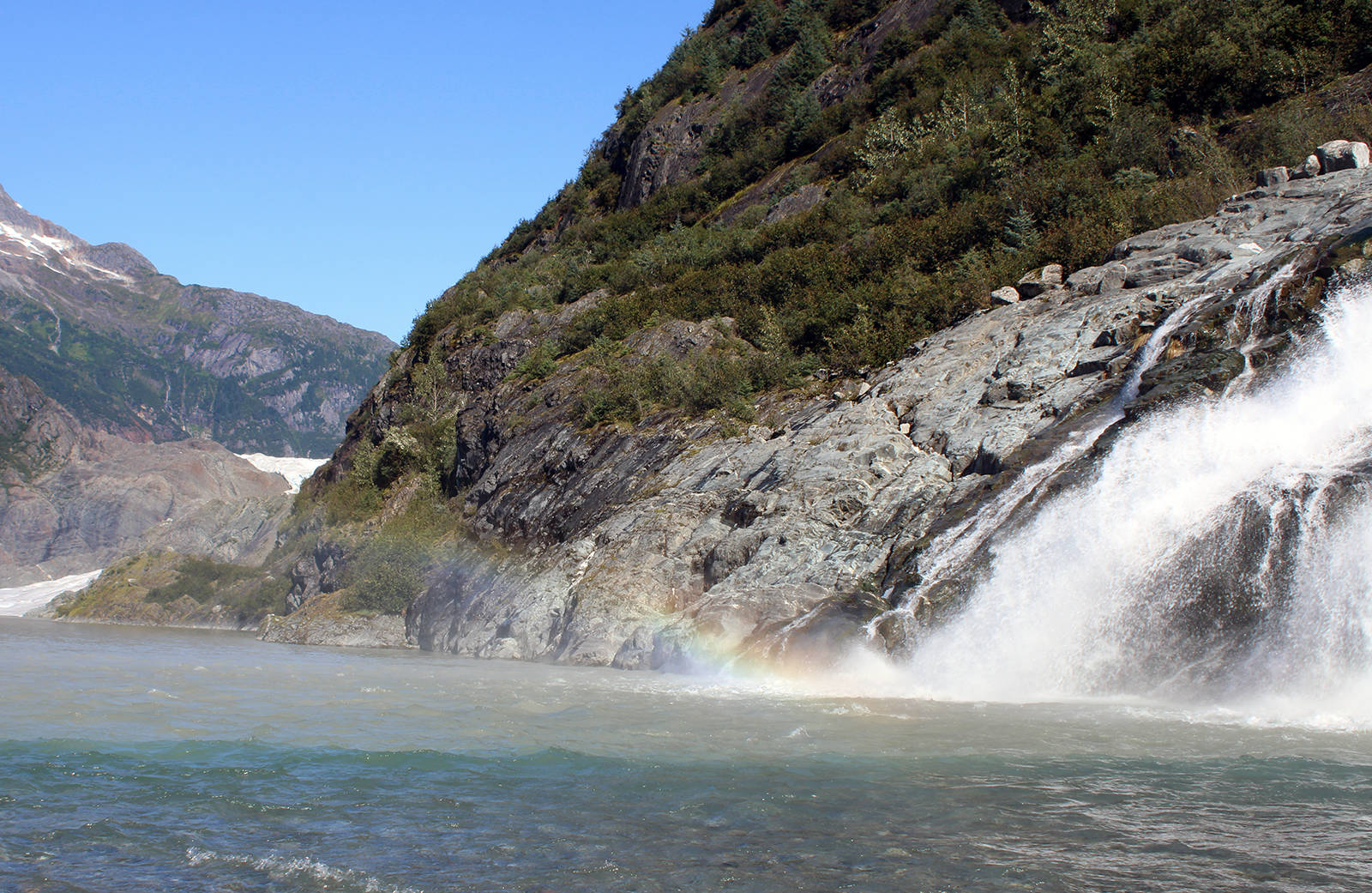 """This Sept. 6, 2020, photo shows mist from Nugget Falls refracting light to create a prism-like effect. """"Like many children I watched this summer, mine enjoyed climbing the glacially smoothed rock slopes up to the visitor center or down to the water at Photo Point. And hiking to Nugget Falls,"""" writes columnist Rich Moniak. (Ben Hohenstatt / Juneau Empire)"""