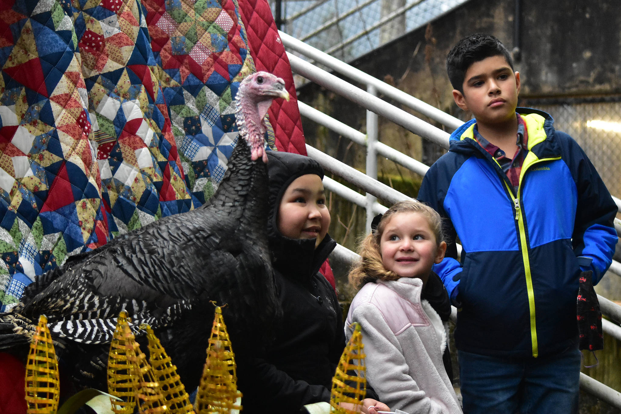 Peter Segall / Juneau Empire From right to left, Braden De Varny, 11; Cat De Varny, 4; Tazlina Heckman, 9; and a turkey have their photo taken outside Juneau-Douglas High School: Yadaa.at Kalé on Wednesday for a fundraiser for the school's vocational programs.