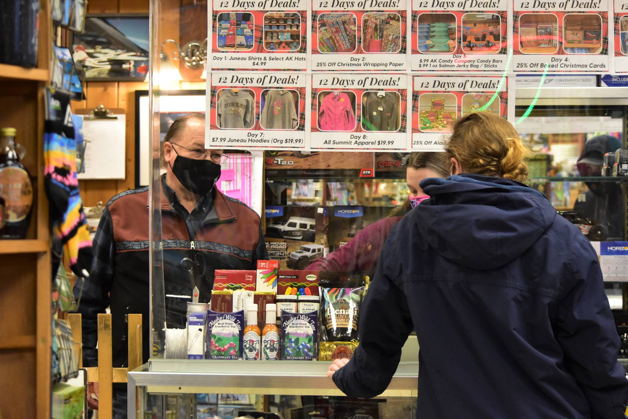 Mike Wiley, left, and daughter Megan Bishop serve a customer at their store, Ben Franklin Store, in downtown Juneau on Tuesday, Dec. 15, 2020. The city extended its mask mandate at a meeting Monday, but Wiley and Bishop said they'd ask customers to wear a mask regardless of the mandate. (Peter Segall / Juneau Empire)