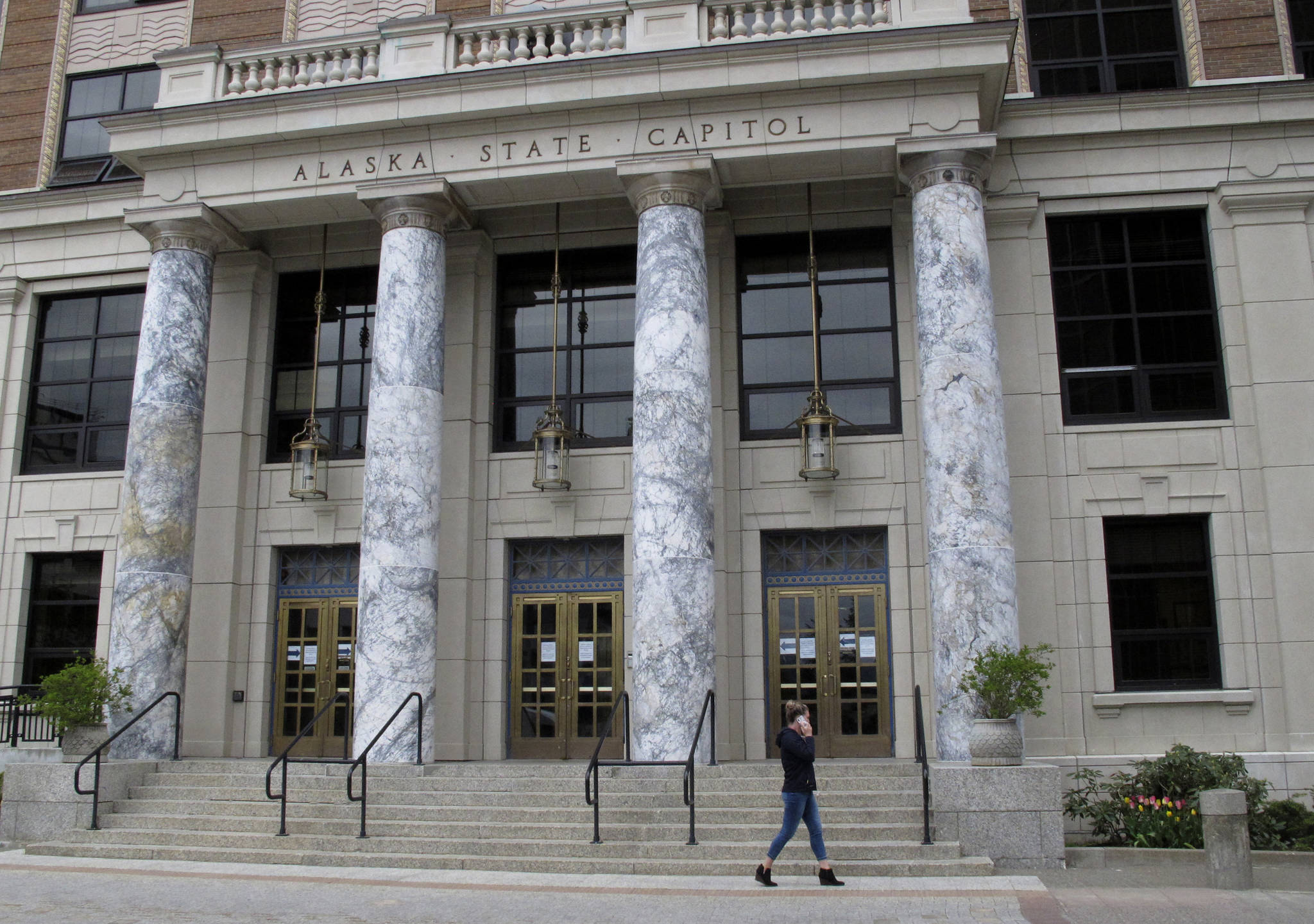 A woman walks past the Alaska Capitol in Juneau. Alaska lawmakers are set to convene amid a near decade-long run of deficits and economic fallout from the ongoing coronavirus pandemic. Go-to reserve accounts are depleted, and tough decisions await on how to use the state's nest-egg oil-wealth fund. It's unclear who will lead those debates: neither the House nor the Senate has organized. (AP Photo / Becky Bohrer)