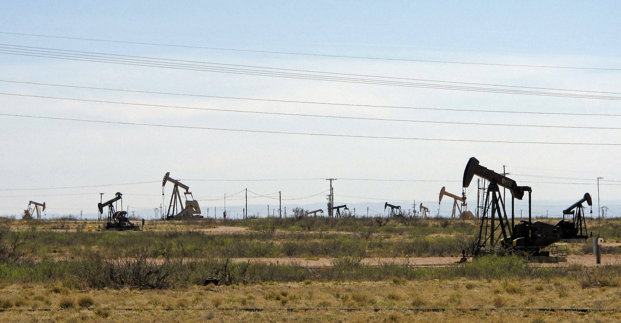 Oil rigs stand in the Loco Hills field on U.S. Highway 82 in Eddy County near Artesia, N.M., one of the most active regions of the Permian Basin. President Joe Biden is set to announce a wide-ranging moratorium on new oil and gas leasing on U.S. lands, as his administration moves quickly to reverse Trump administration policies on energy and the environment and address climate change. (AP Photo/Jeri Clausing, File)