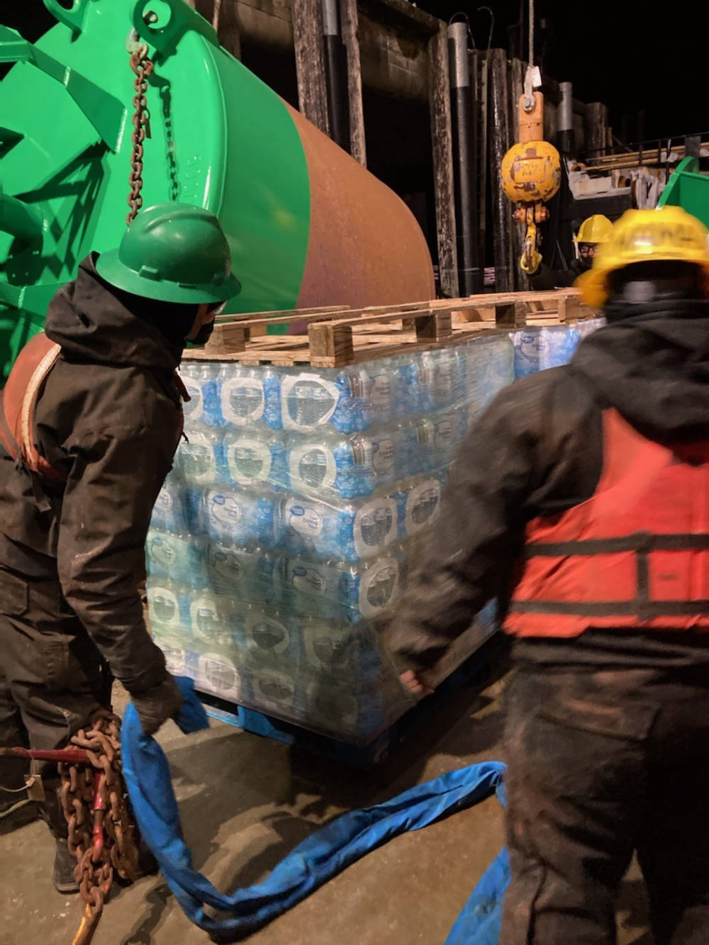 Coast Guard Cutter Hickory crewmembers offload pallets of water destined for the residents in Angoon, Alaska, Feb. 14, 2021. (U.S. Coast Guard photo)