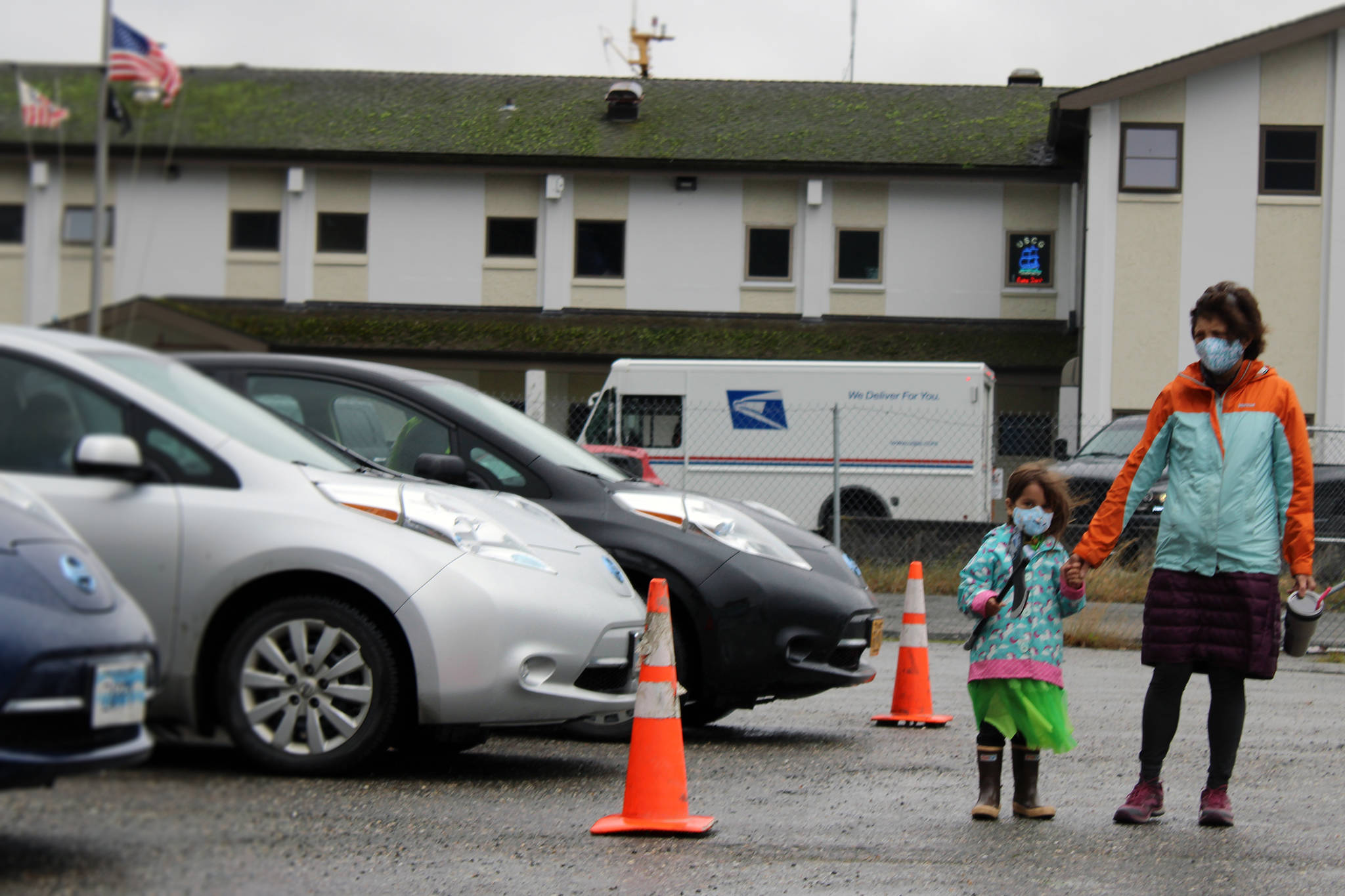 Nathea Burnet holds both a plastic ax and her grandmother, Patricia Forrest's, hand while looking at electric vehicles during Juneau Electric Vehicle Association's road rally Saturday, Sept. 26, 2020. On a per capita basis, there is one electric vehicle per 76 residents in Juneau. There were 418 EVs registered in Juneau as of November 2020. (Ben Hohenstatt / Juneau Empire File)