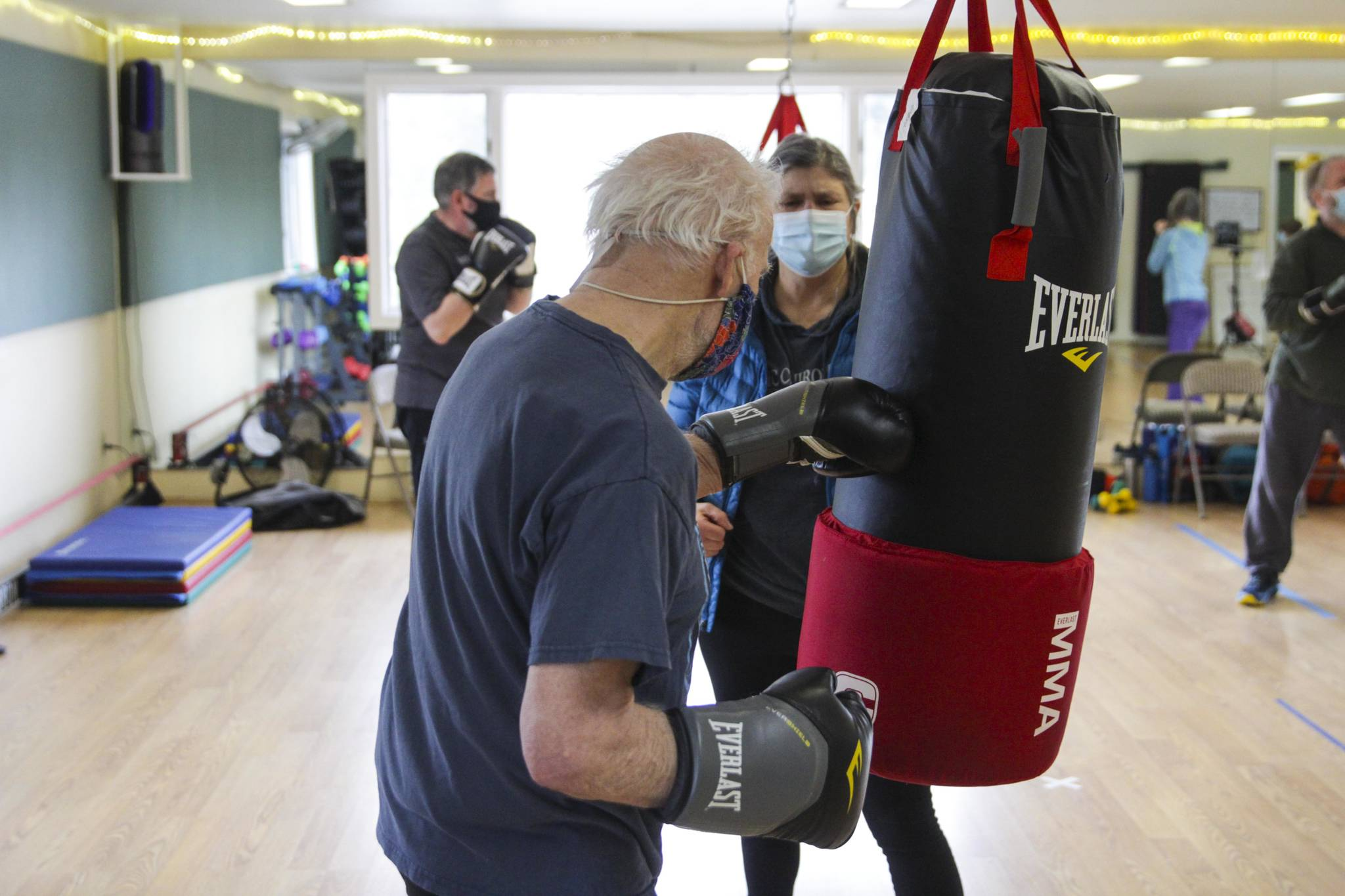 Steve Wolf strikes a punching bag as his wife Bev Ingram holds it during a boxing class designed to help fight back against the symptoms Parkinson's disease through a specific regimen at Pavitt Health and Fitness on March. 2, 2021. (Michael S. Lockett / Juneau Empire)