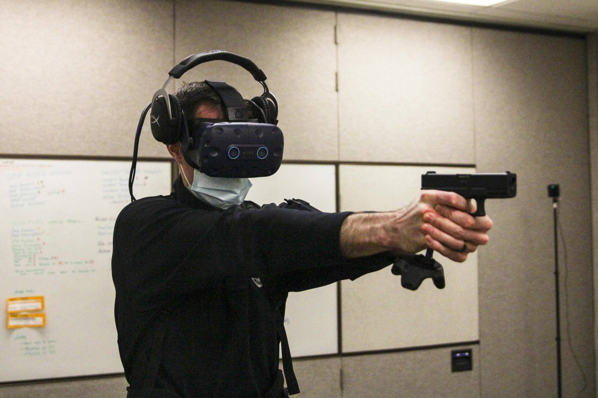 Michael S. Lockett / Juneau Empire Detective Patrick Taylor draws a sidearm-controller Wednesday during a VR training simulation as Sgt. Sterling Salisbury controls the scenario from a computer elsewhere.