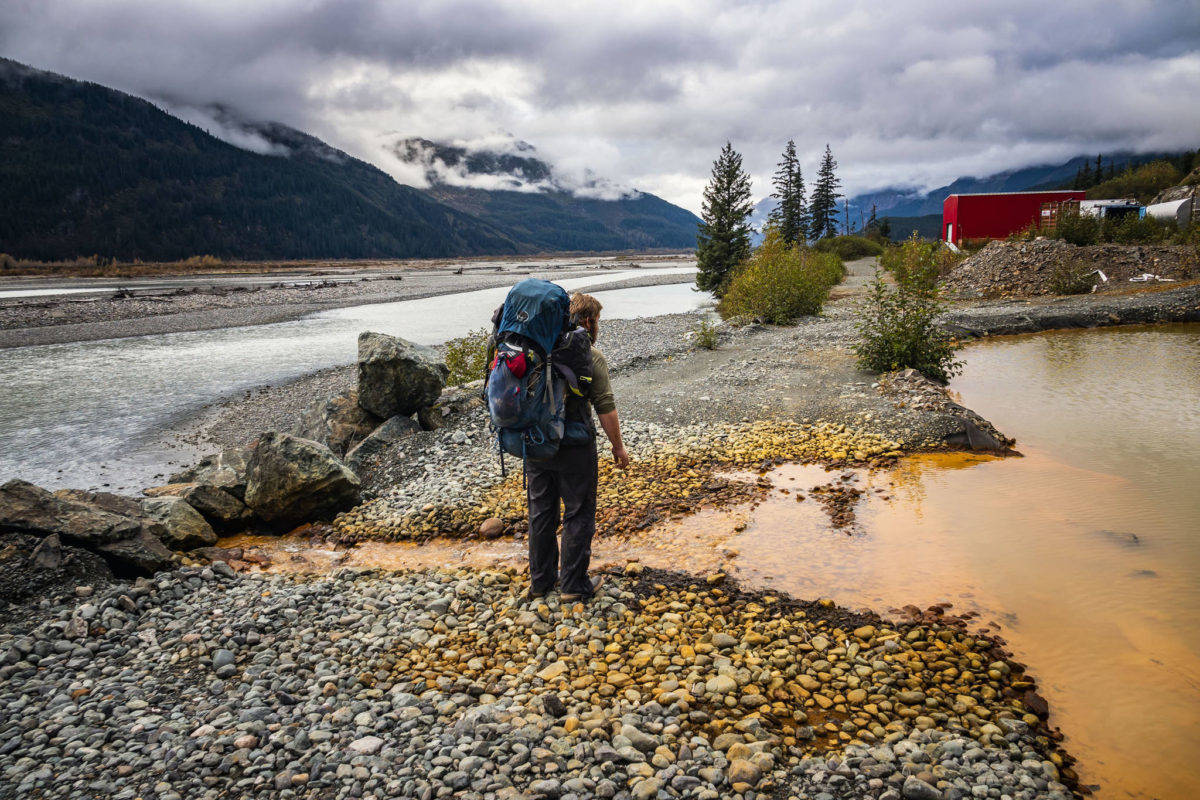 Courtesy Photo / Chris Miller  In this October 2018 photo, Bjorn Dihle inspects the acid mine drainage flowing into the Tulsequah River from a containment pond filled by effluent from the Tulsequah Chief Mine in British Columbia, Canada.