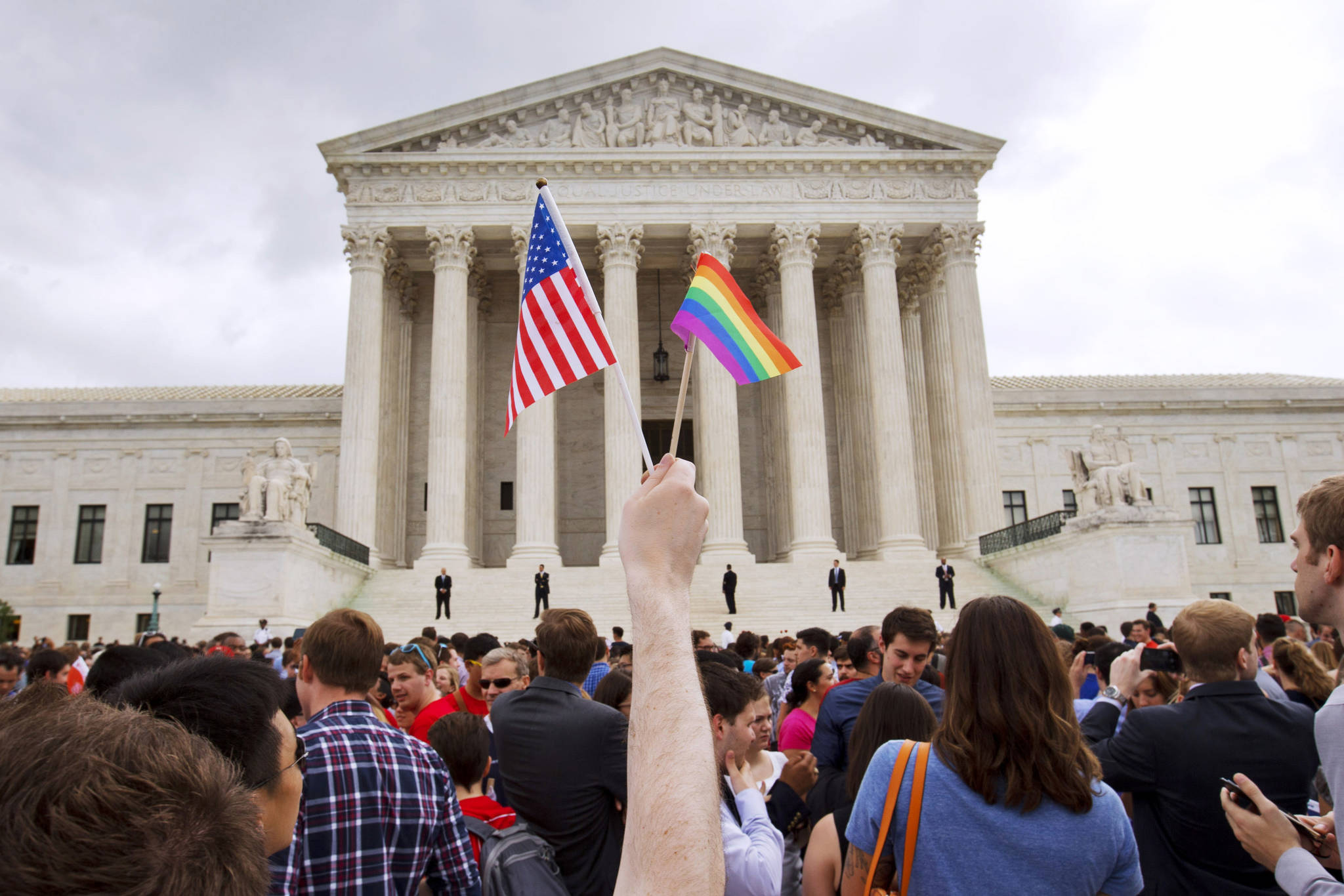 A man holds a U.S. and a rainbow flag outside the Supreme Court in Washington in 2015 after the court legalized gay marriage nationwide. Court documents show the state of Alaska for years maintains a discriminatory policy that denied some same-sex spouses benefits by wrongly claiming gay marriage was not recognized in Alaska, long after courts ordered they be recognized. (AP Photo / Jacquelyn Martin)