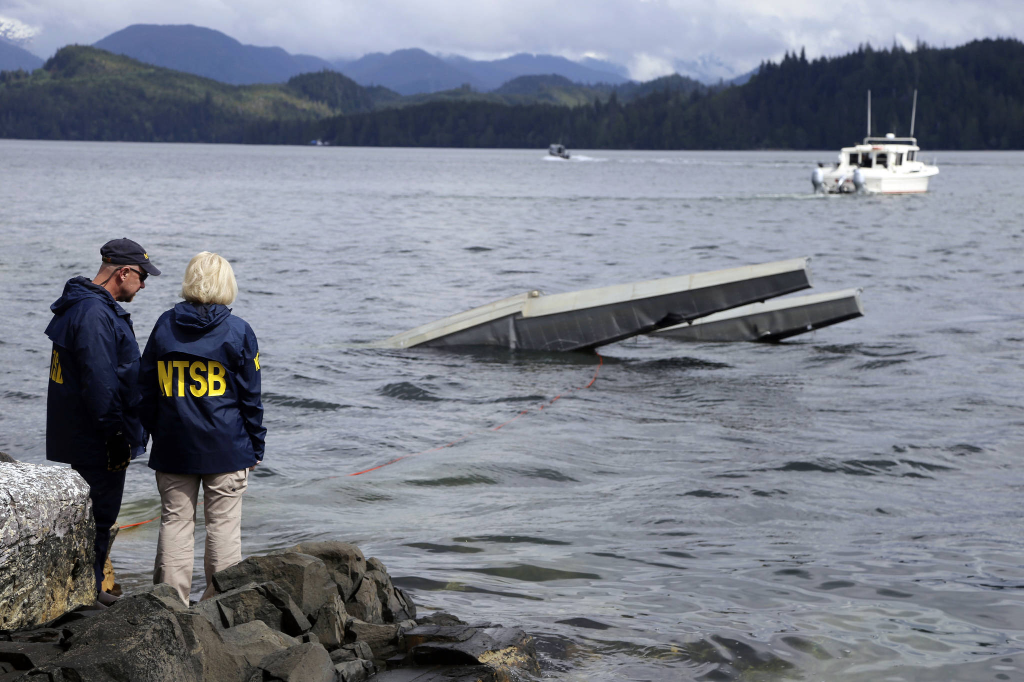 NTSB investigator Clint Crookshanks, left, and member Jennifer Homendy stand near the site of some of the wreckage of the DHC-2 Beaver, Wednesday, May 15, 2019, that was involved in a midair collision near Ketchikan, Alaska, a couple of days earlier. The pilots of two Alaskan sightseeing planes that collided in midair couldn't see the other aircraft because airplane structures or a passenger blocked their views, and they didn't get electronic alerts about close aircraft because safety systems weren't working properly. That's what the staff of the National Transportation Safety board found in their investigation. (Peter Knudson / NTSB)