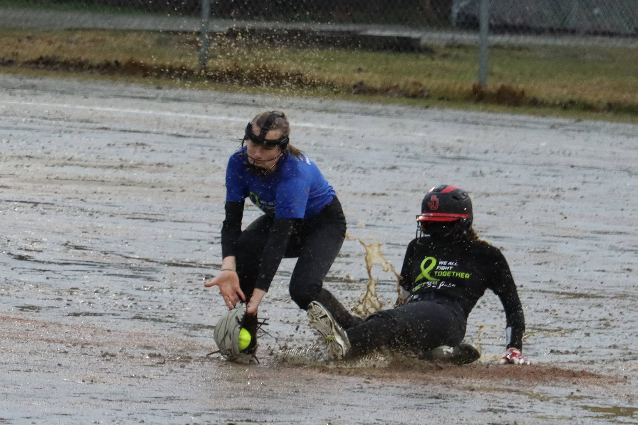 JDHS' Gloria Bixby slides safe into second base and under the tag of TMHS' Jenna Dobson during the first inning of a drizzly Friday night game against Thunder Mountain High School. JDHS leaped out to a 7-0 lead in the first inning and wound up winning 15-0. (Ben Hohenstatt / Juneau Empire)