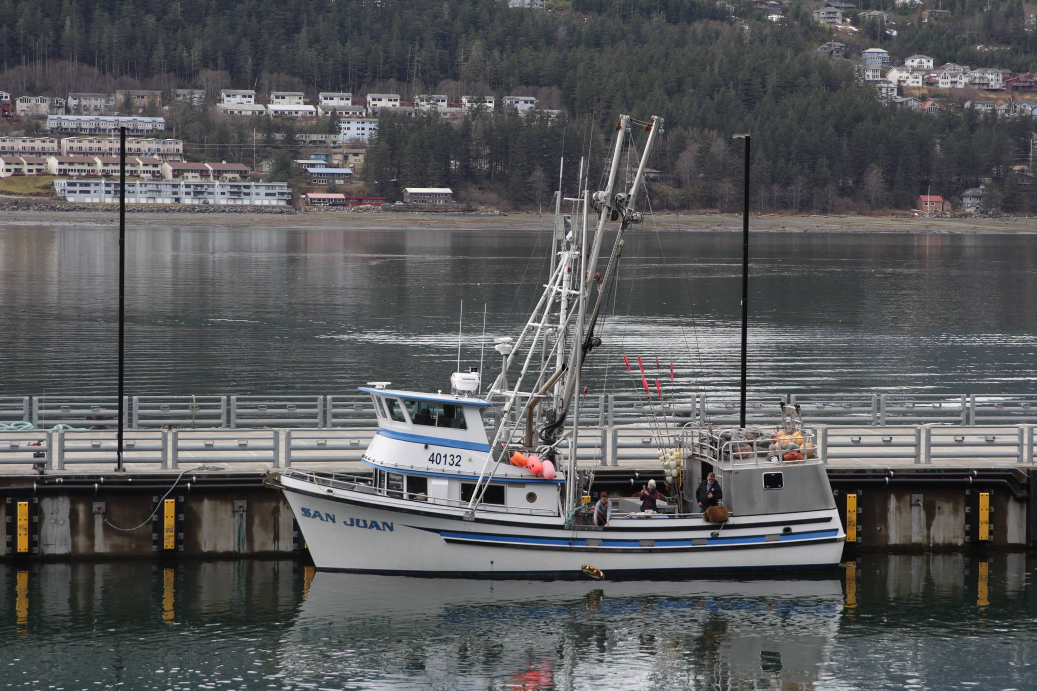 The crew of the fishing vessel San Juan release a memorial wreath into the Gastineau Channel during the 31st annual Blessing of the Fleet and Reading of Names at the Alaska Commercial Fishermen's Memorial in Juneau on May 1, 2021. (Michael S. Lockett / Juneau Empire)