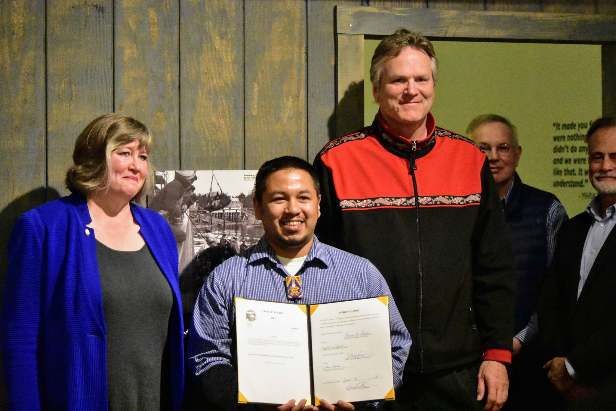 From left to right, Rep. Sara Hannan, D-Juneau; Martin Stepetin Sr. and Gov. Mike Dunleavy at a signing ceremony for a bill protecting a cemetery in Funter Bay at the Juneau-Douglas City Museum on Tuesday, June 8, 2021. (Peter Segall / Juneau Empire)