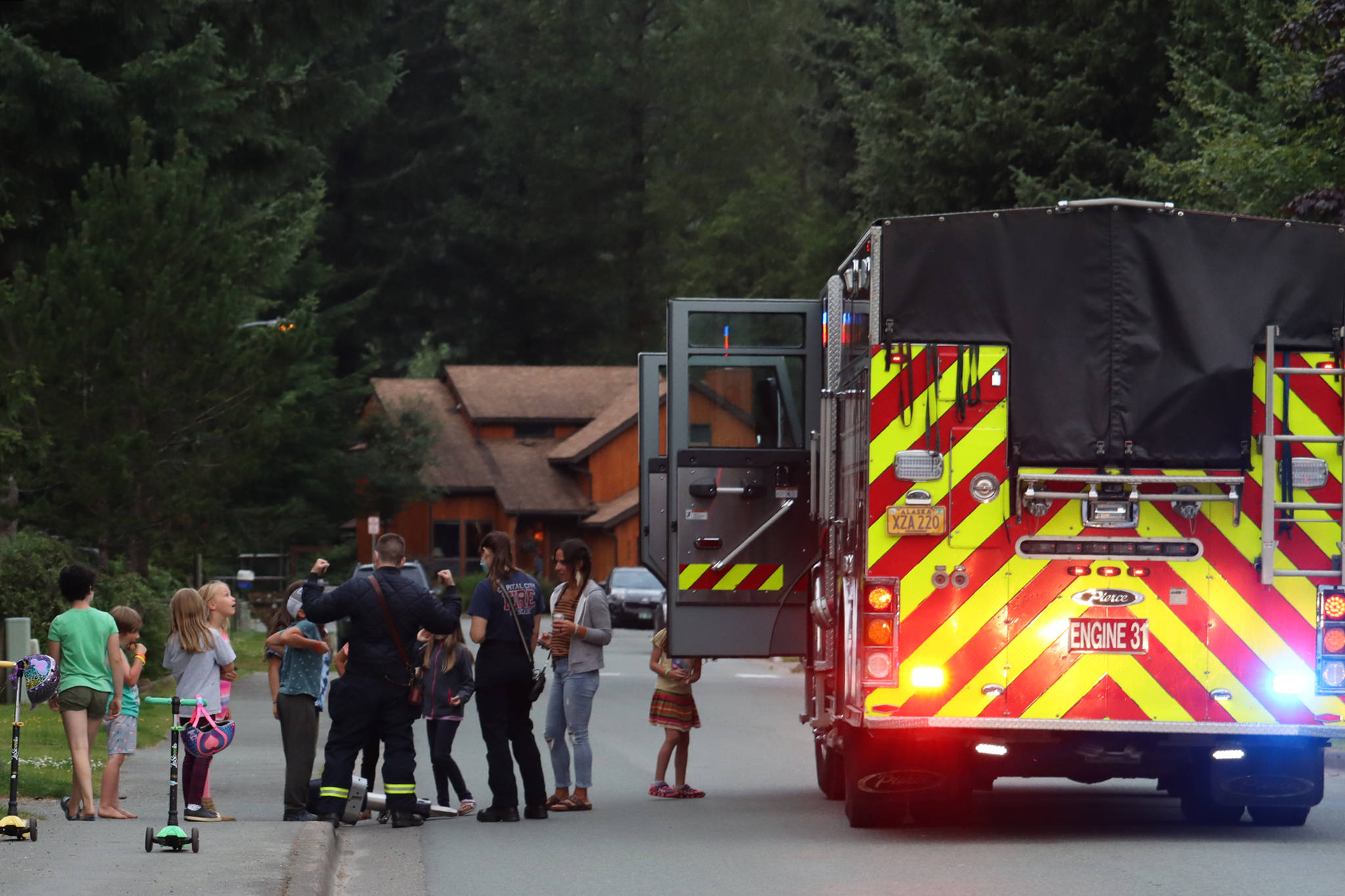 Children line up to check out a fire truck during National Night Out. Sirens, horns and squawking intercoms were part of the night's soundscape. (Ben Hohenstatt / Juneau Empire)