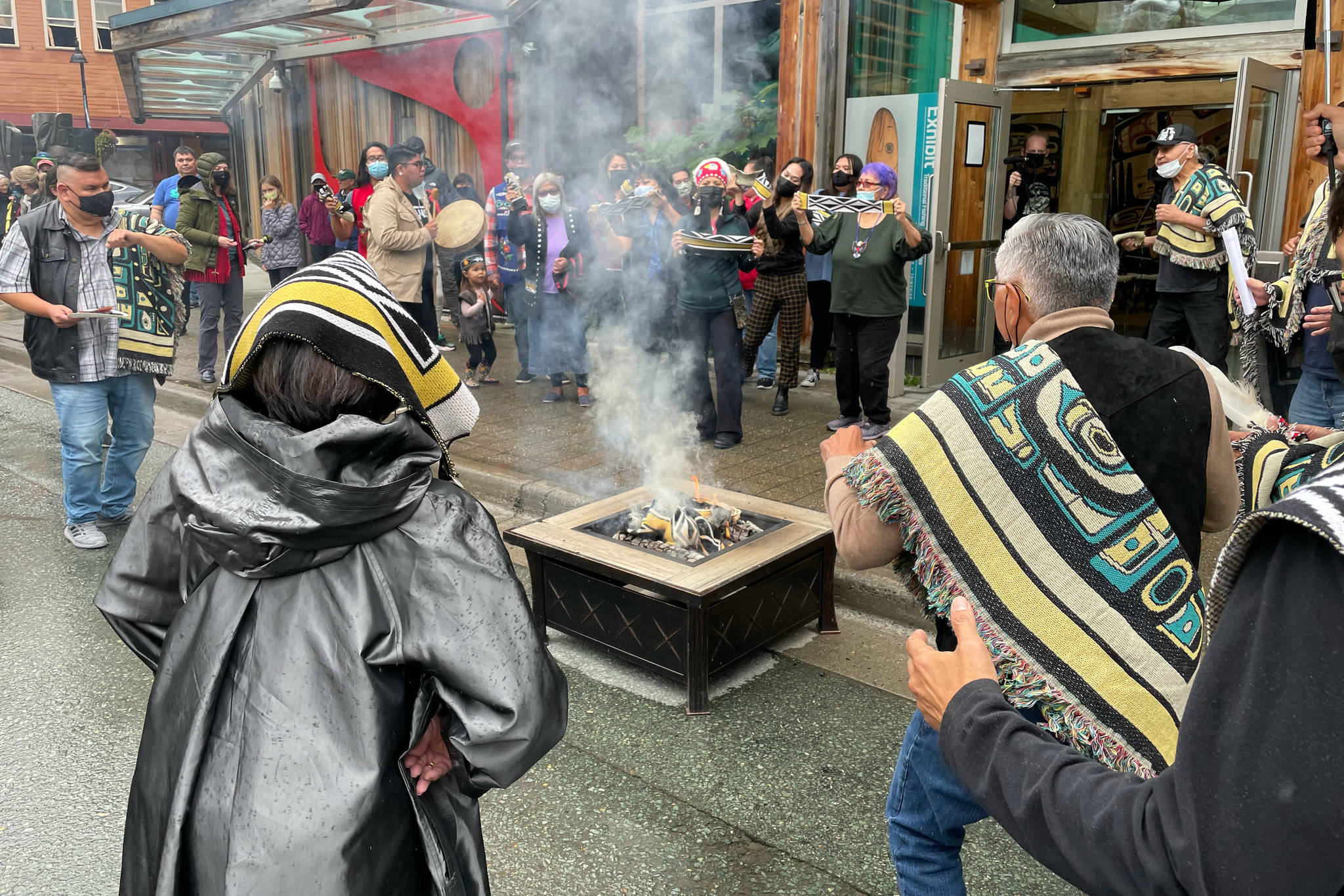 Michael S. Lockett / Juneau Empire  Participants burn an example of a commercial garment that led to a now-settled intellectual property lawsuit in a ceremony commemorating the settlement with the fashion company on Friday, Aug. 13, 2021.