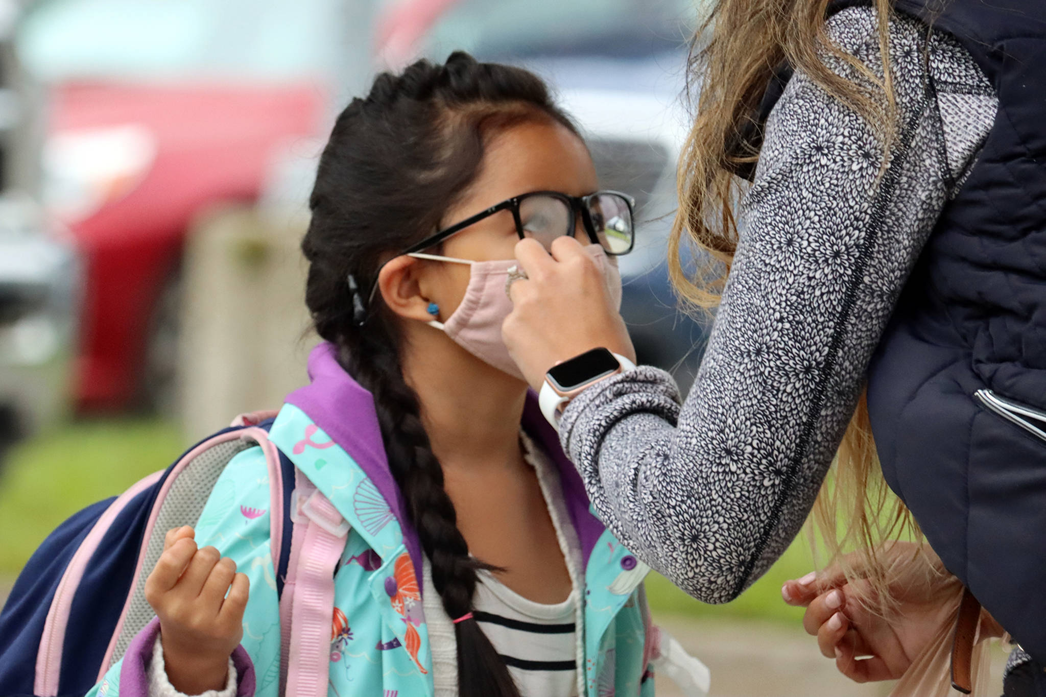 Vanessa Dickinson adjusts second grade student Kanani Dickinson's mask ahead of the first day of school. Kanani Dickinson is a student at Auke Bay Elementary School. Vanessa Dickinson said she's excited the 7-year-old is back in school. (Ben Hohenstatt / Juneau Empire)