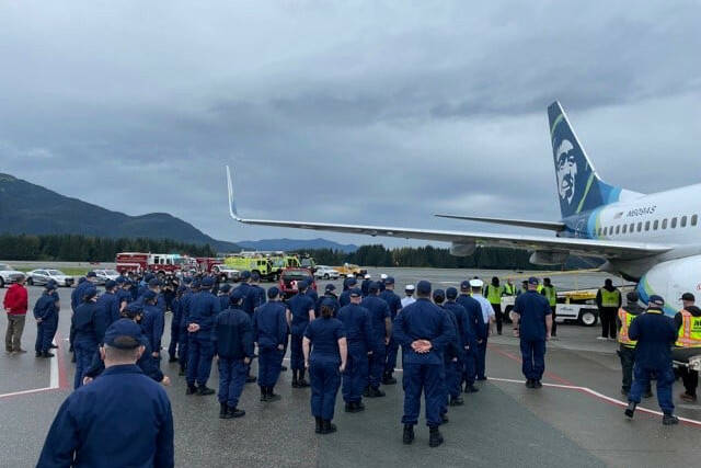 Coast Guardsmen stand in formation at Juneau International Airport as the body of Chief Petty Officer Jeffery DeRonde, who died over the weekend, is loaded on an airplane on Sept. 7, 2021. (Courtesy photo / Capital City Fire/Rescue)